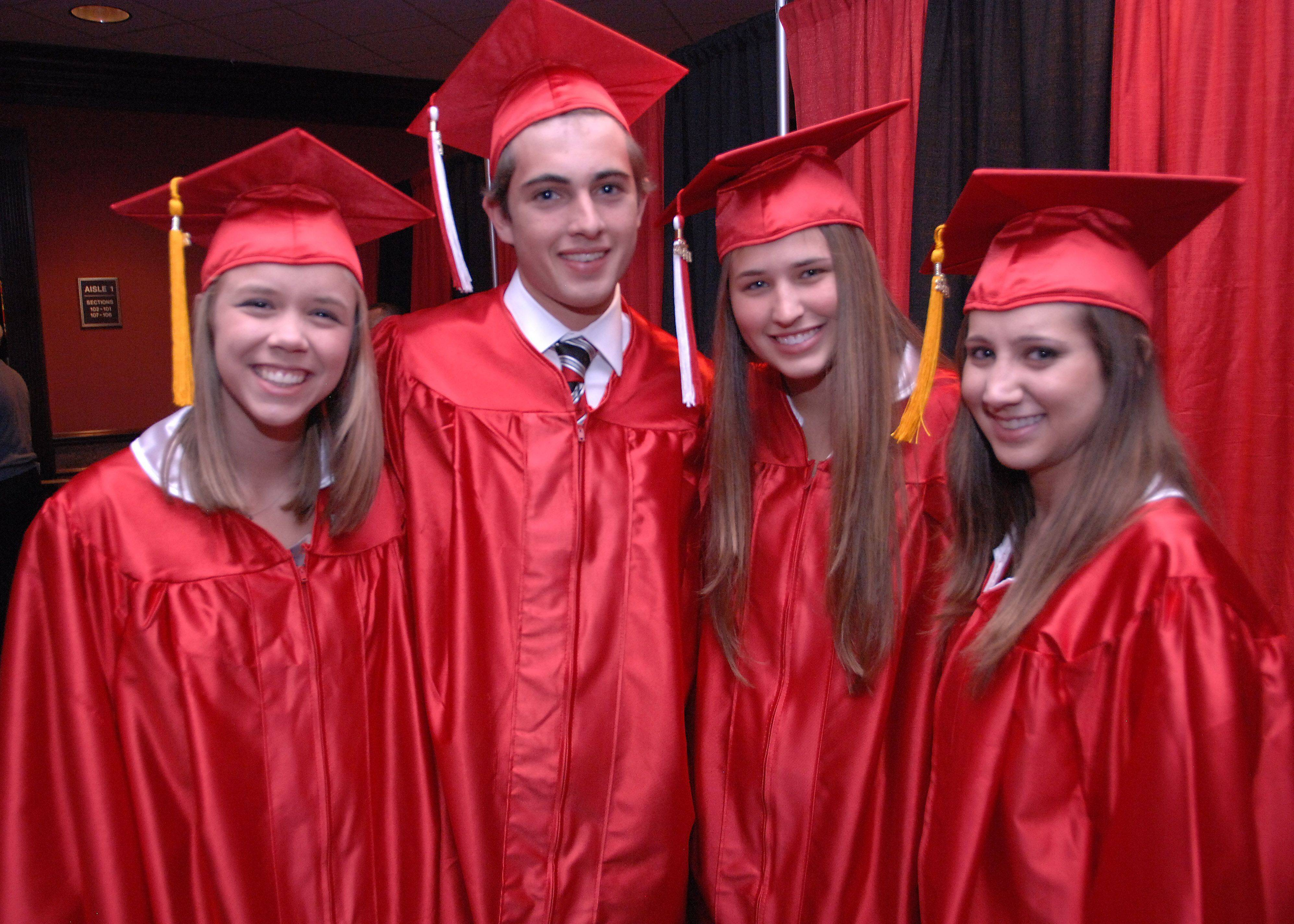 Maine South soon-to-be graduates Lydia Ramsey, Jack Purdy Jr., Elisabeth Roames and Nicole Roman prepare to march into the Rosemont Theatre for their commencement.