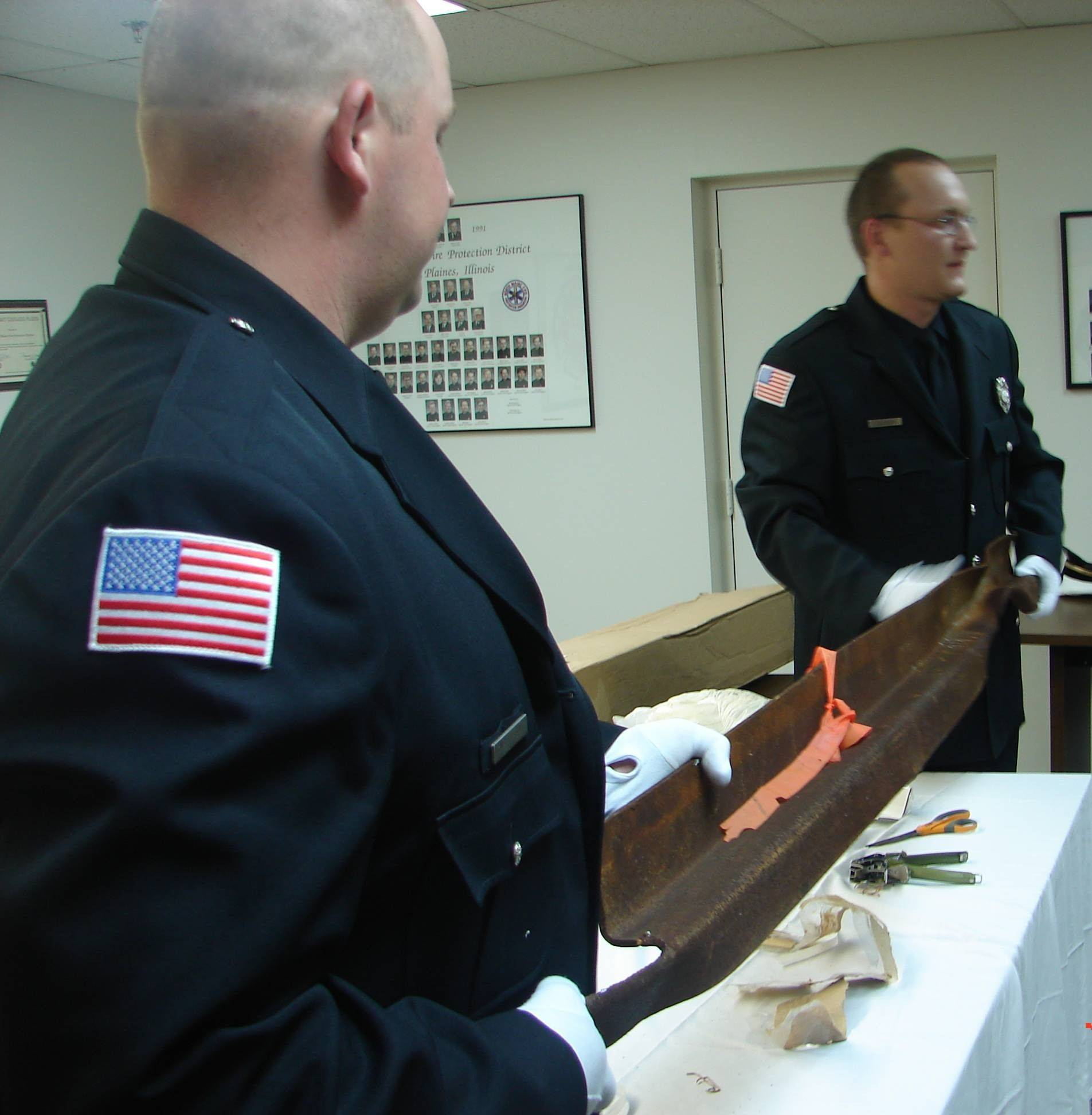 Firefighter/paramedics Nick Rusz, left, and Greg Zalewski hold up a piece of steel from the World Trade Center towers unveiled by the North Maine Fire Protection District during a public event this week. The beam will become part of a memorial at Ridgewood Cemetery in Des Plaines.