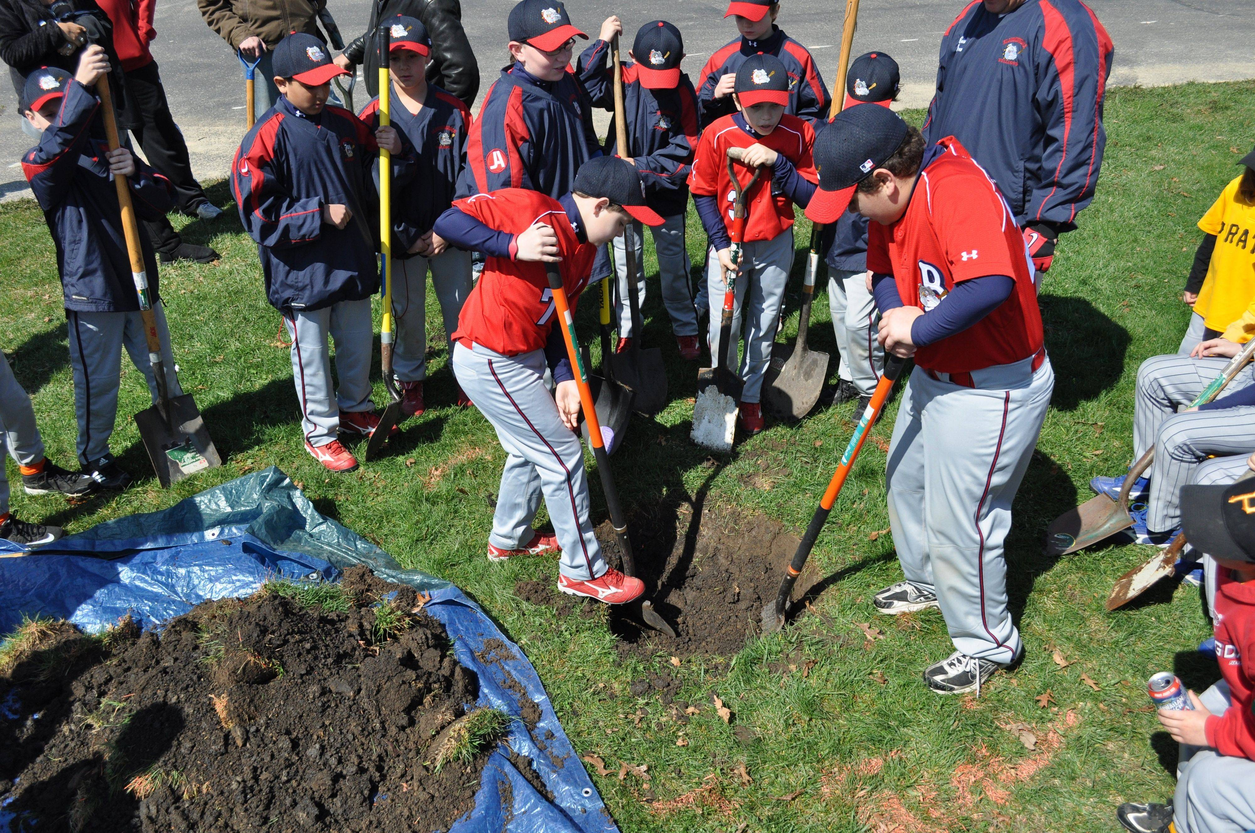Members of the Bloomingdale Bulldogs traveling baseball team dig a hole where a flagpole memorial was placed in honor of Sgt. Jean Claude Nolan.