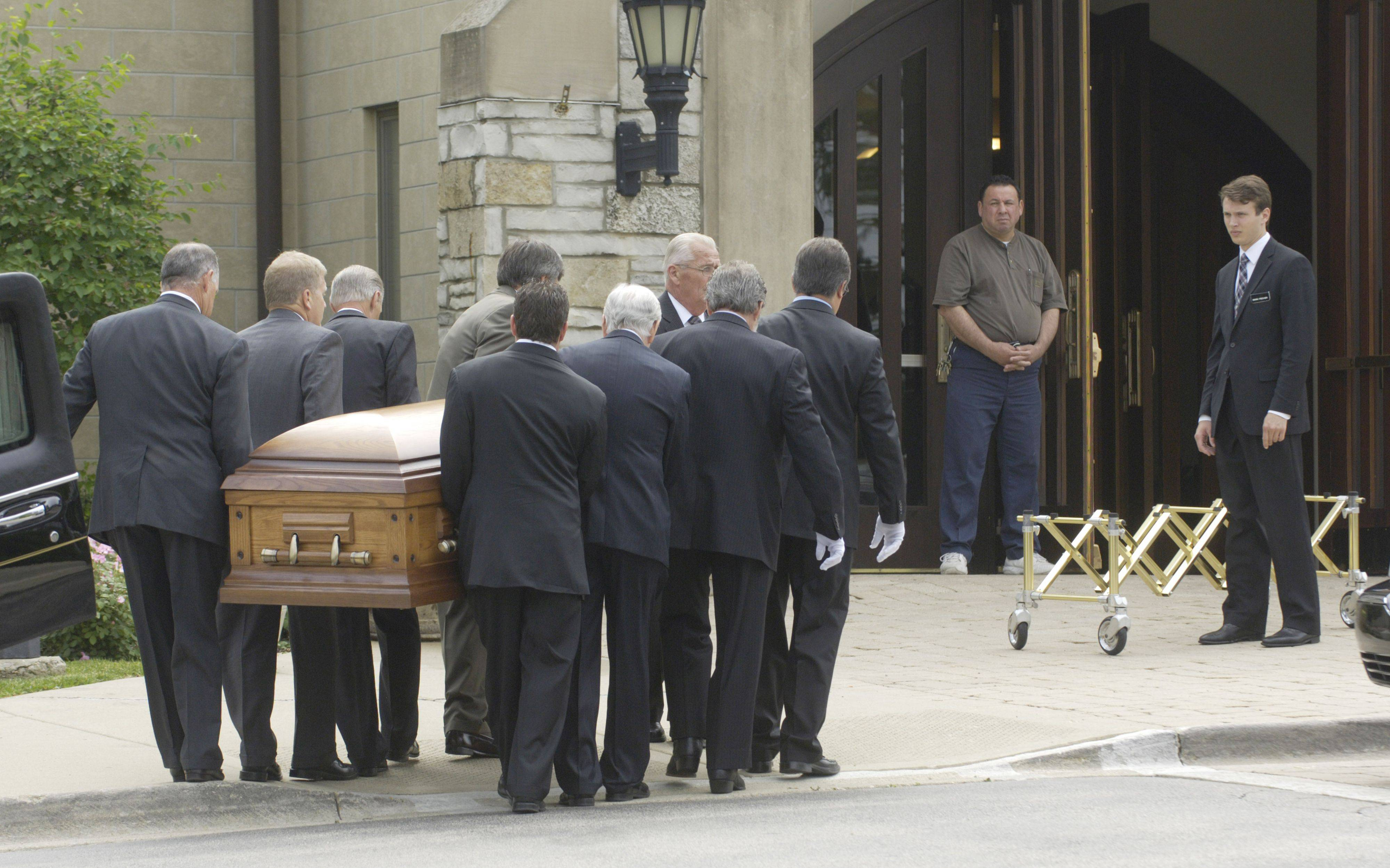 Pallbearers carry the casket from the hearse into St. Anne Catholic Church in Barrington.