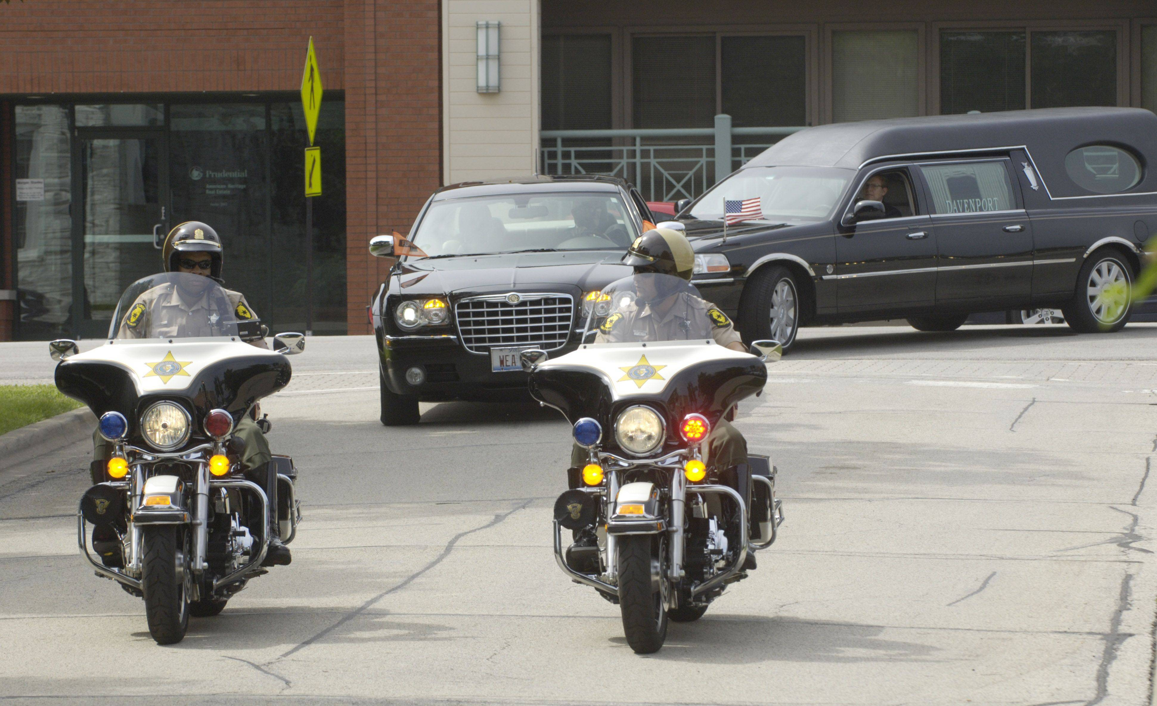 Illinois State Police officers on motorcycles lead the hearse carrying state Rep. Mark Beaubien to St. Anne Catholic Church in Barrington.