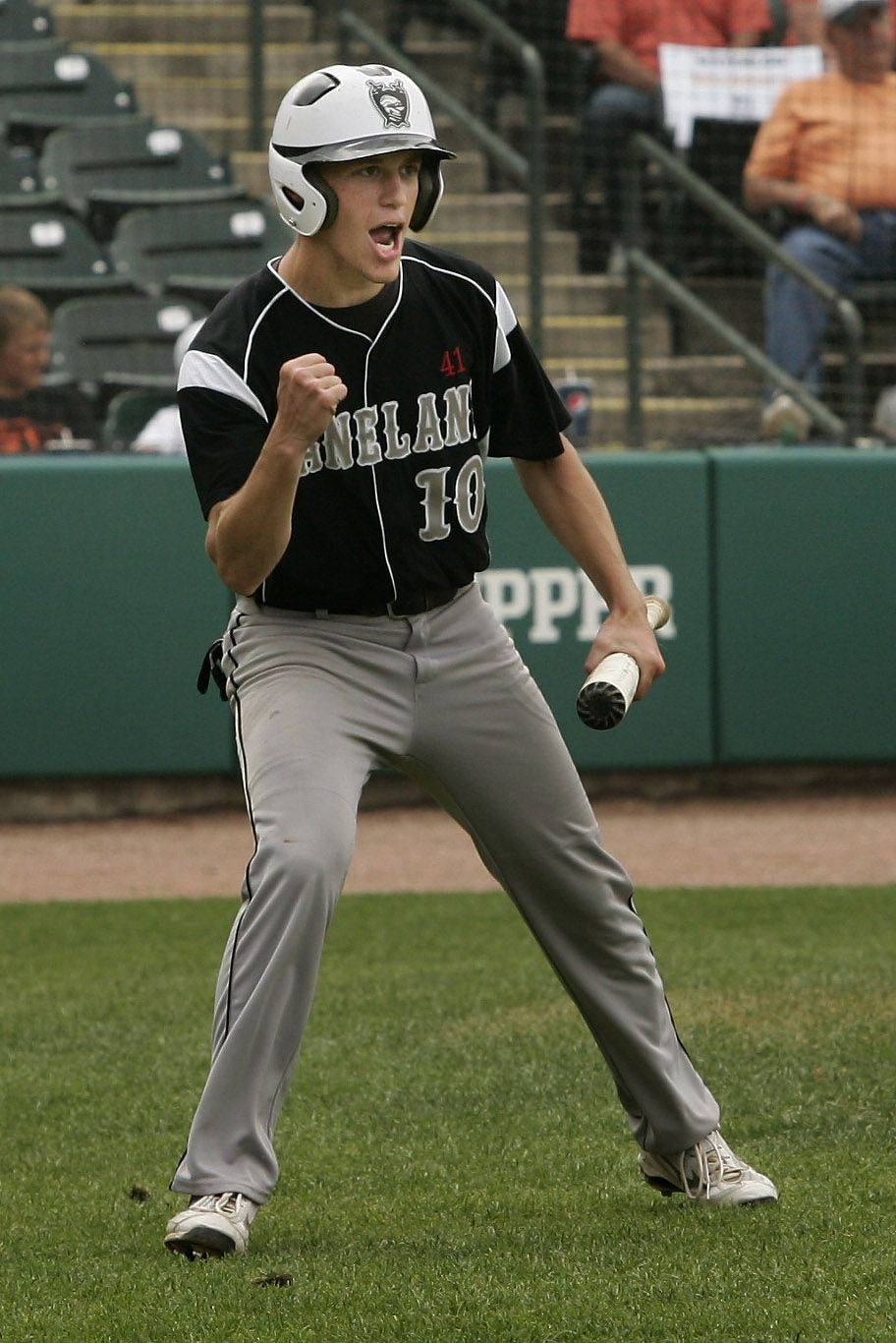 Kaneland runner Corey Landers cheers on his teammates after scoring a run at Silver Cross Field in Joliet.