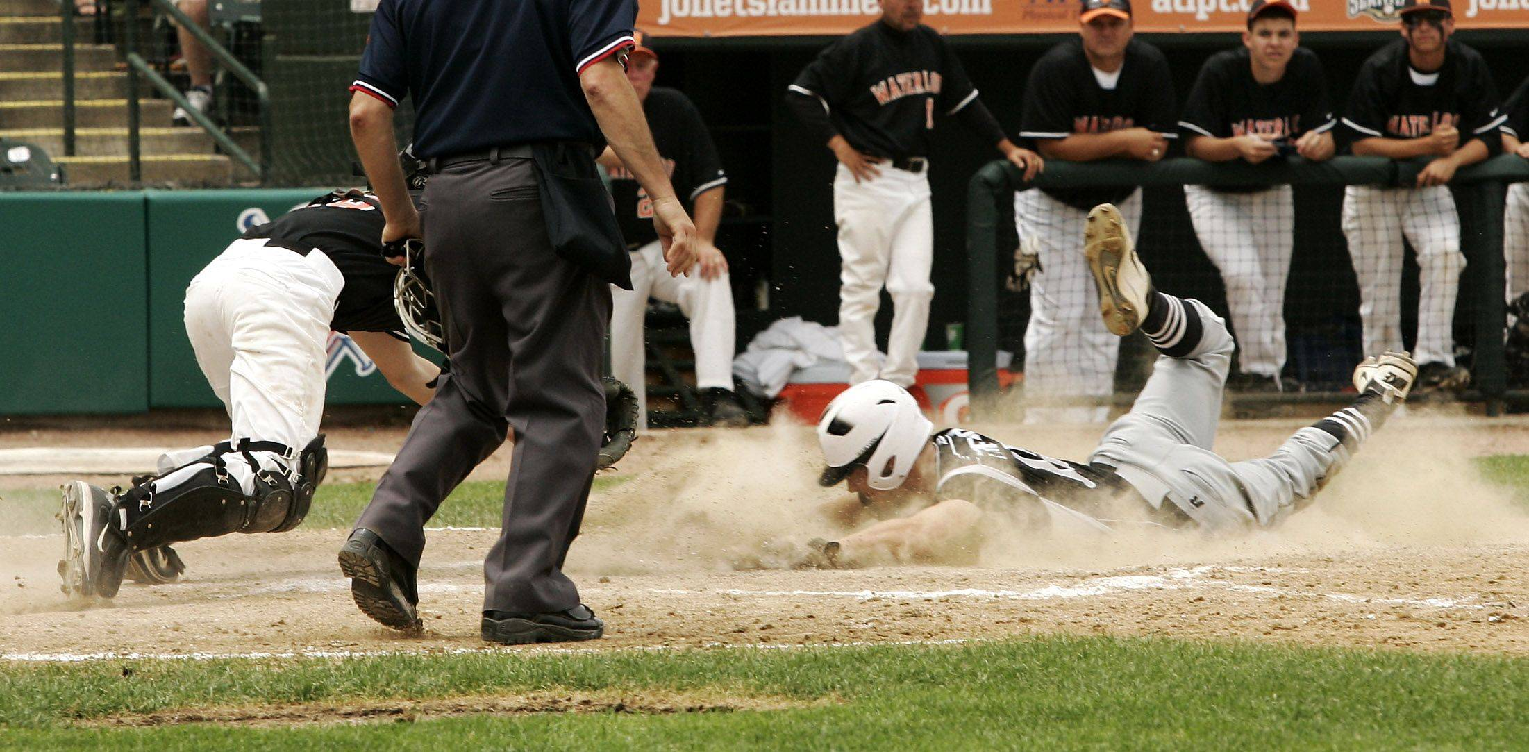 Kaneland runner Drew French slides safely under the tag at home by Waterloo catcher Lucus Wetzler .