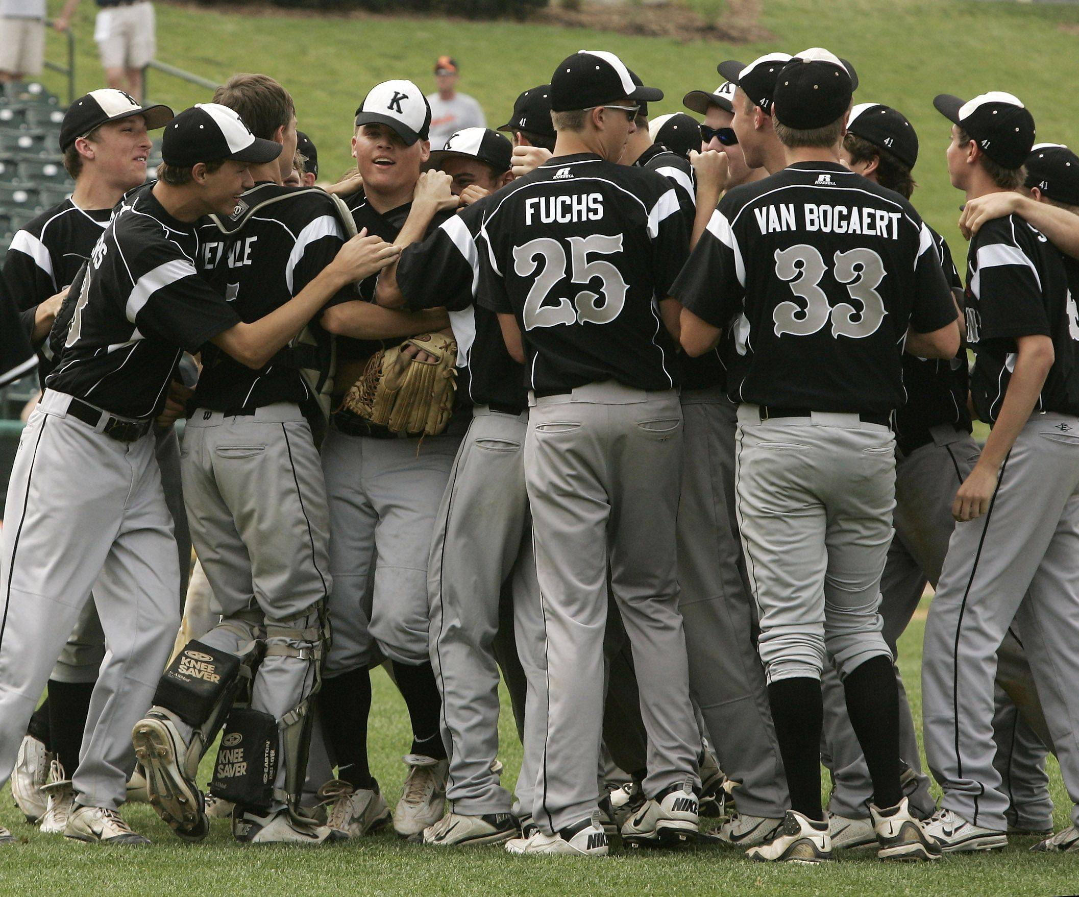 Kaneland players swarm pitcher Bobby Thorson, hat tilted, after their win against Waterloo.