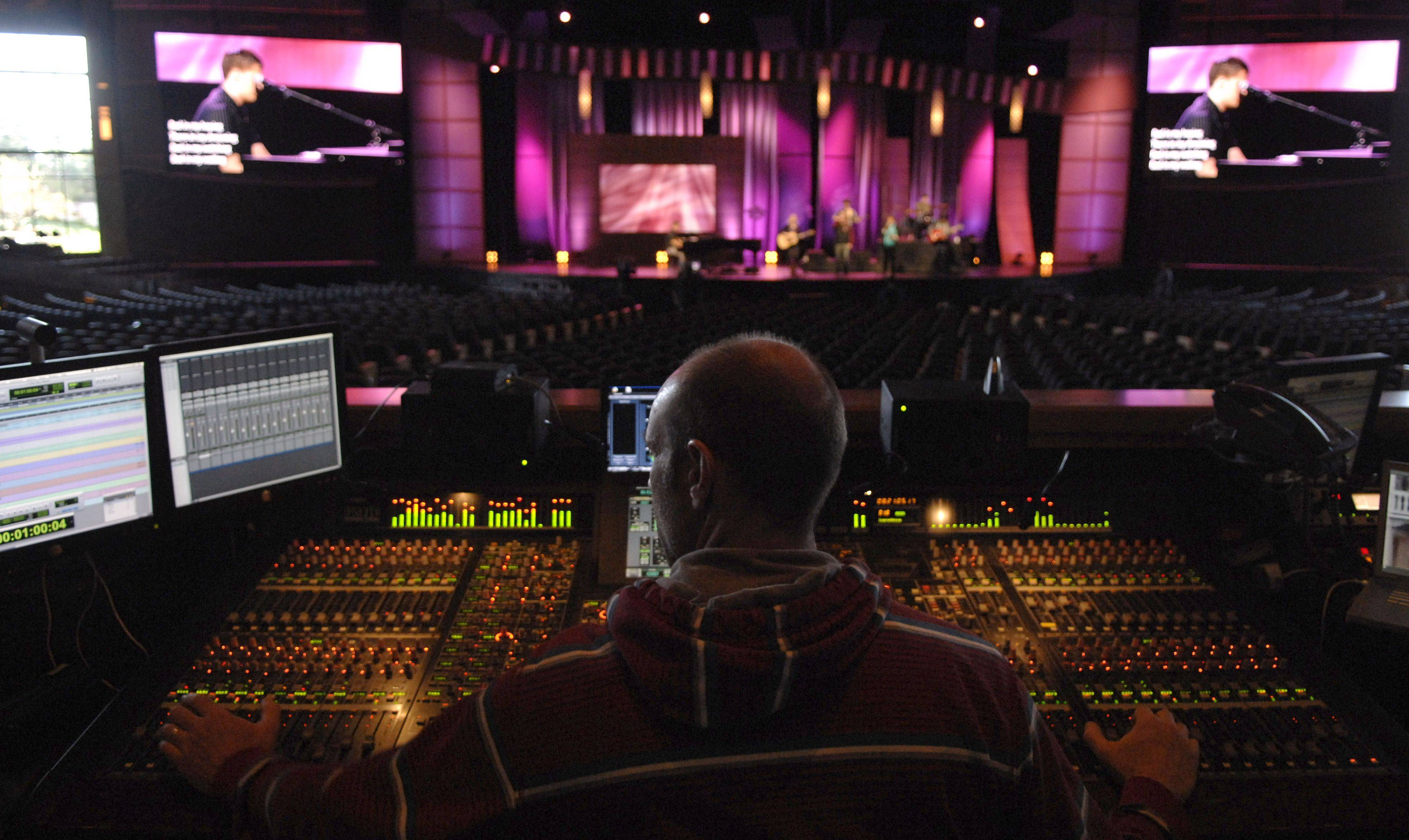 Staff audio engineer Ron Cook controls the mixing board during a full rehearsal at Willow Creek before the first service of the day.