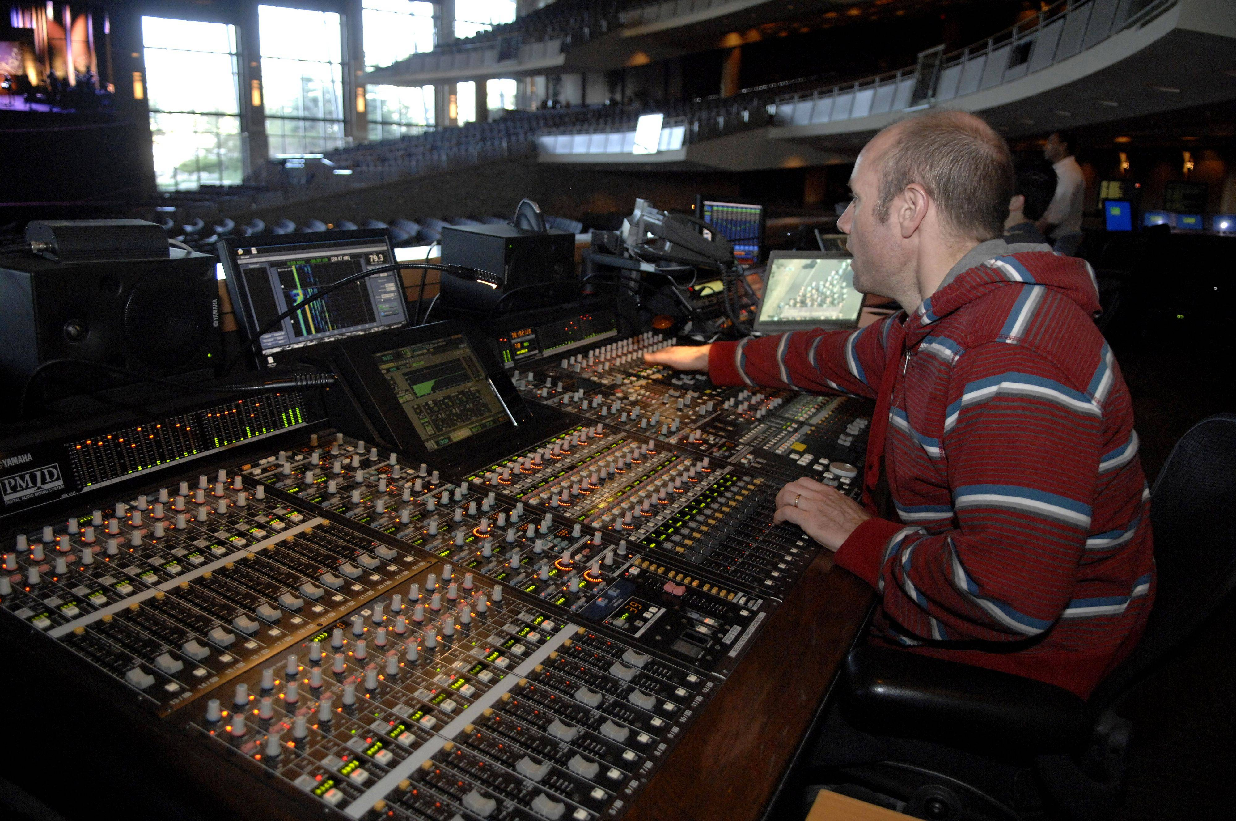Staff audio engineer Ron Cook controls the mixing board during a full rehearsal at Willow Creek Church in South Barrington before the first service of the day.
