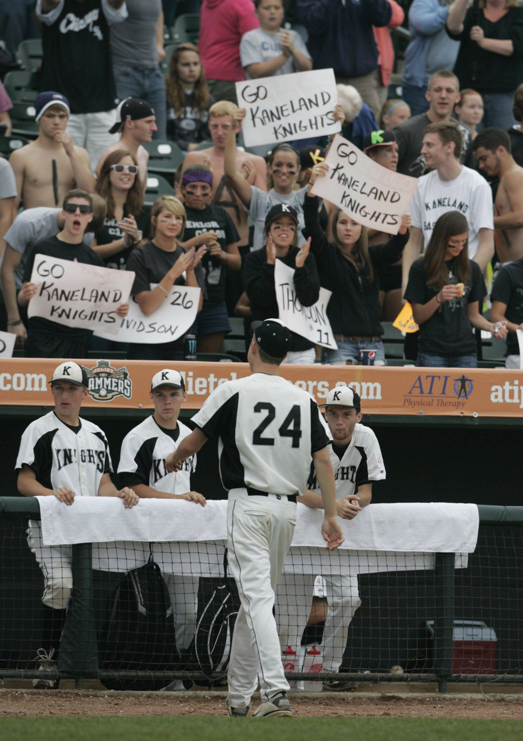 Kaneland fans cheer on the team as Trevor Heinle walks to the dugout during the Kaneland vs. Oak Forest boys high school baseball game Saturday in the Class 3A state finals at Silver Cross Field in Joliet. Kaneland defeated Oak Forest 11-3 to win the state championship.