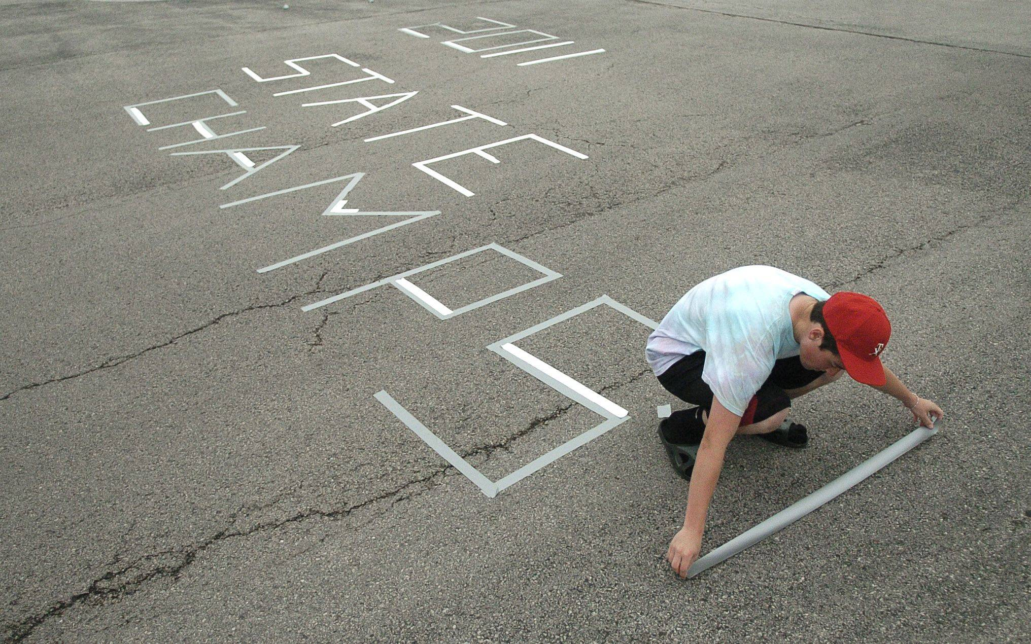 Blake Sowell, 16, puts the finishing touches of a duct tape sign in the parking lot that he and his mom, Roxey (cq), made to welcome home the 3A state baseball champs of Kaneland High School on Saturday, June 11. Blake played on the sophomore team this past year.