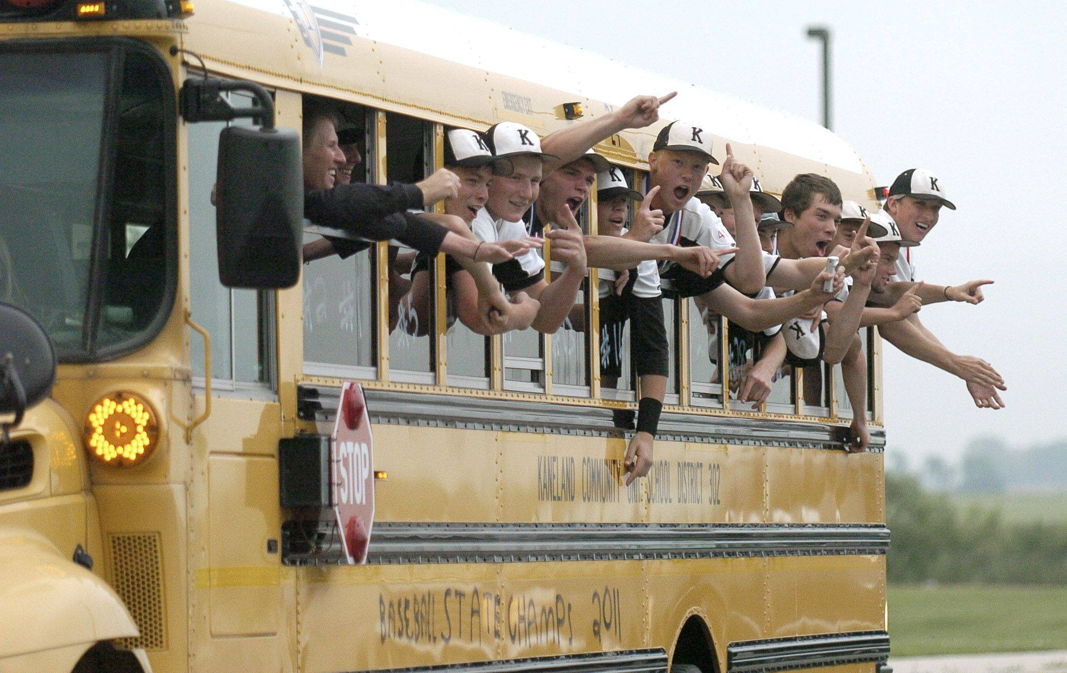 The Kaneland High School 3A state champs varsity baseball team cheers as they hang out the bus window on their return to school during a homecoming parade on Saturday, June 11.