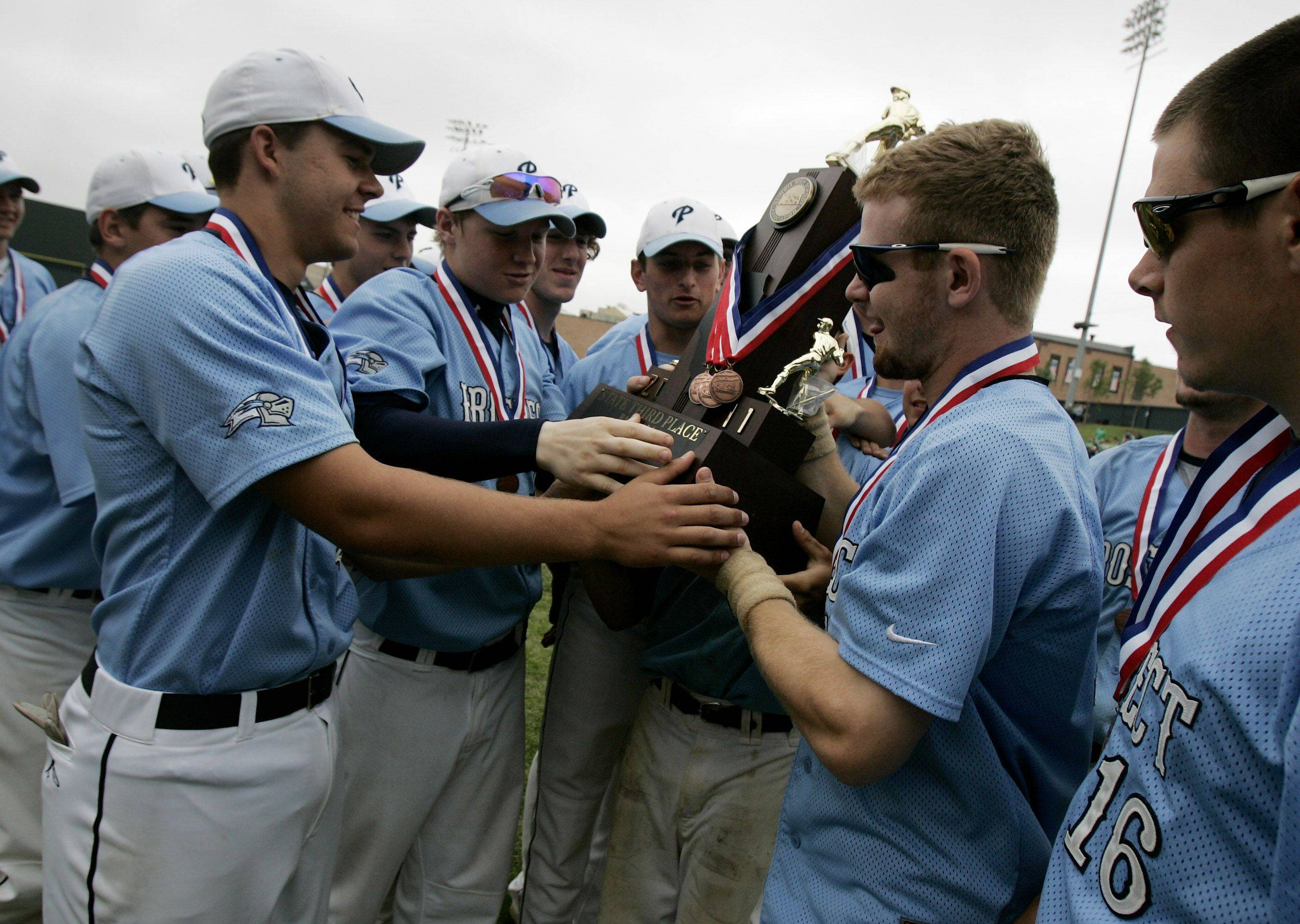 Prospect players touch the third place trophy after defeating Mt. Carmel during the boys high school baseball game Saturday in the Class 4A 3rd place game at Silver Cross Field in Joliet. Prospect defeated Mt. Carmel 2-1 to win third place in the state.
