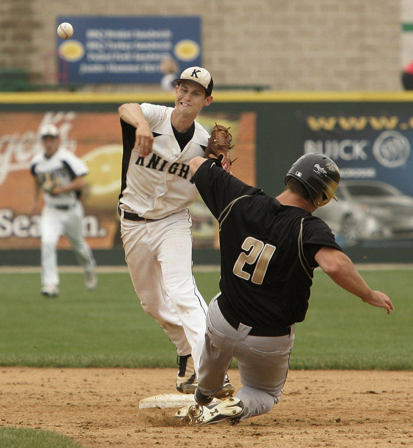 Kaneland shortstop Brian Dixon turns the double play in the seventh inning for the final outs of the game as Oak Forest runner Tim Barry slides into second during the Kaneland vs. Oak Forest boys high school baseball game Saturday in the Class 3A state finals at Silver Cross Field in Joliet. Kaneland defeated Oak Forest 11-3 to win the state championship.
