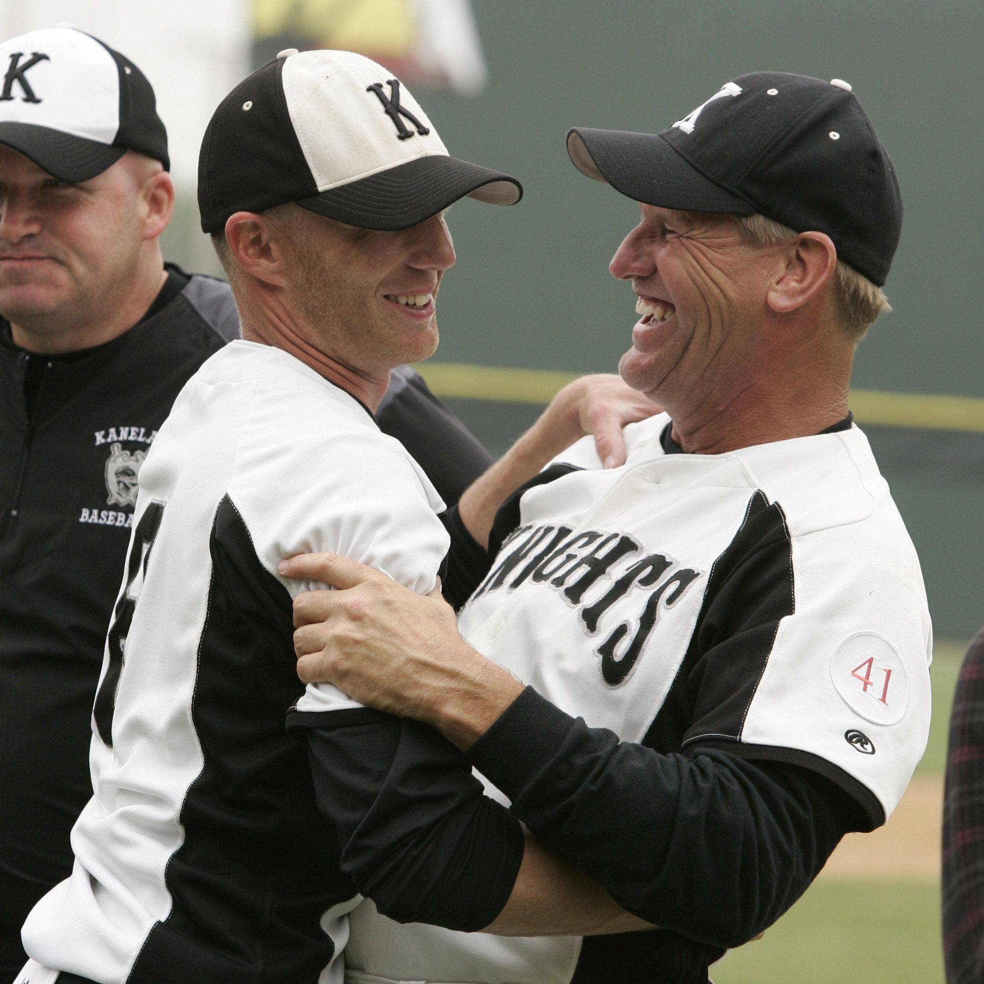 Kaneland coach Brian Aversa, left, and first base coach Jim Smedley hug after defeating Oak Forest boys during the high school baseball game Saturday in the Class 3A state finals at Silver Cross Field in Joliet. Kaneland defeated Oak Forest 11-3 to win the state championship.
