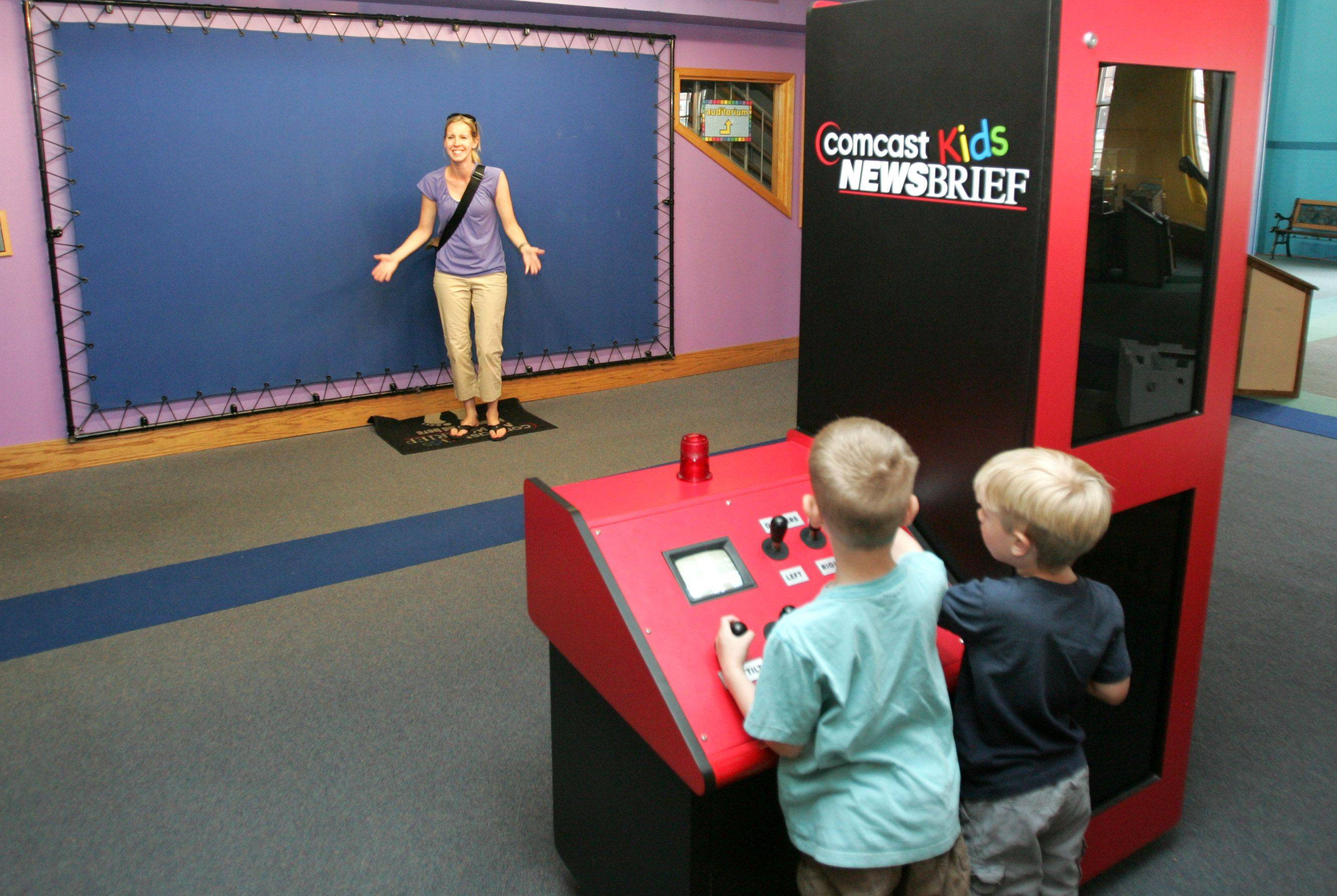 Jennifer Fuhrmann stands on camera for her son Jackson, right, and nephew Luke Petersen, of North Aurora, as they play in a broadcast news exhibit at SciTech Hands-on Museum in Aurora.