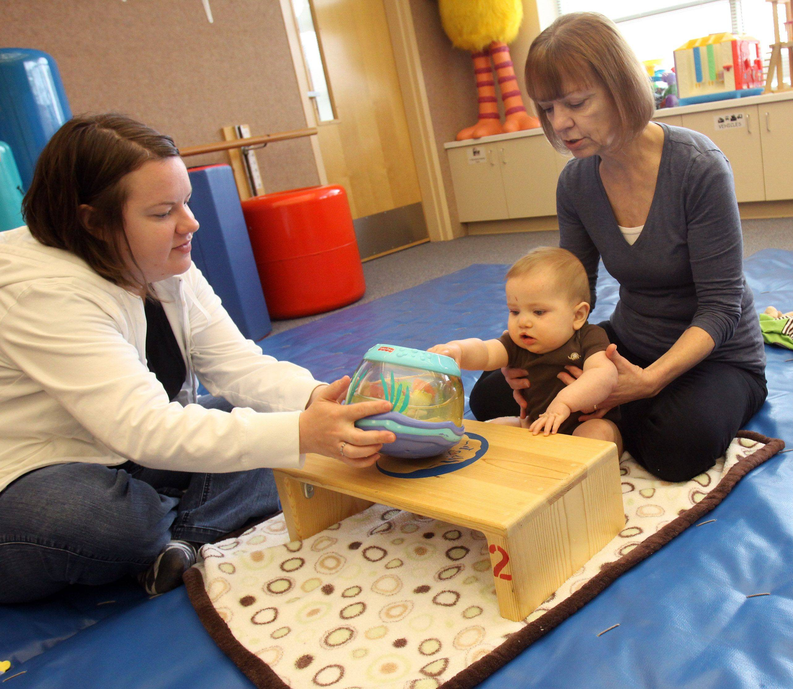 Charlie Feuerborn, 9 months, works with his mom, Allison, left and his therapist Kathe Monley at Easter Seals in Villa Park. Charlie participates in the Make the First Five Count program, which tries to identify potential developmental problems so young children can get therapy.