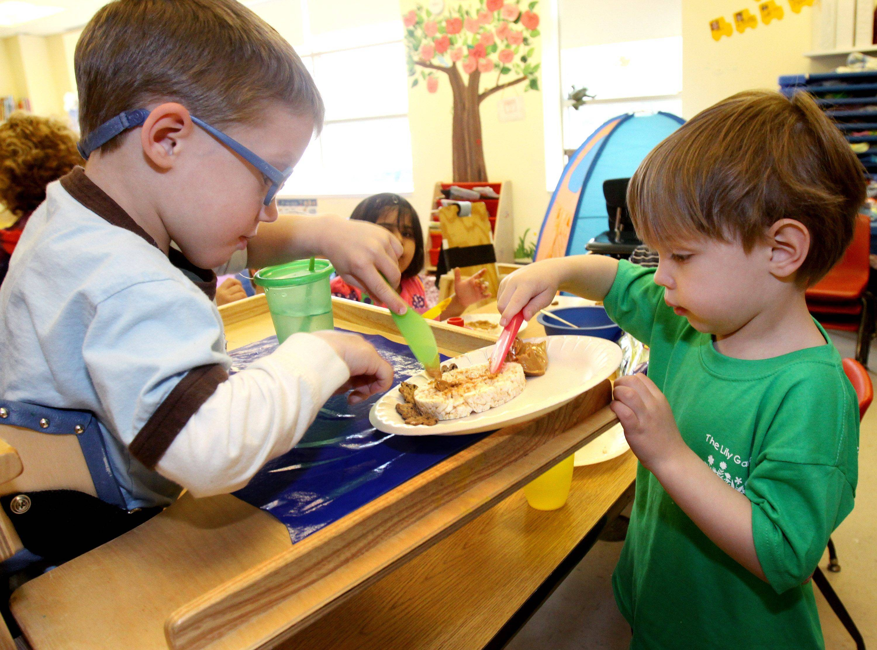 Charlie Krupka, 5, left, gets a little help with spreading his peanut butter from Evan Lopresti, 4, at the Lily Garden all-inclusive child care center at Easter Seals in Villa Park.