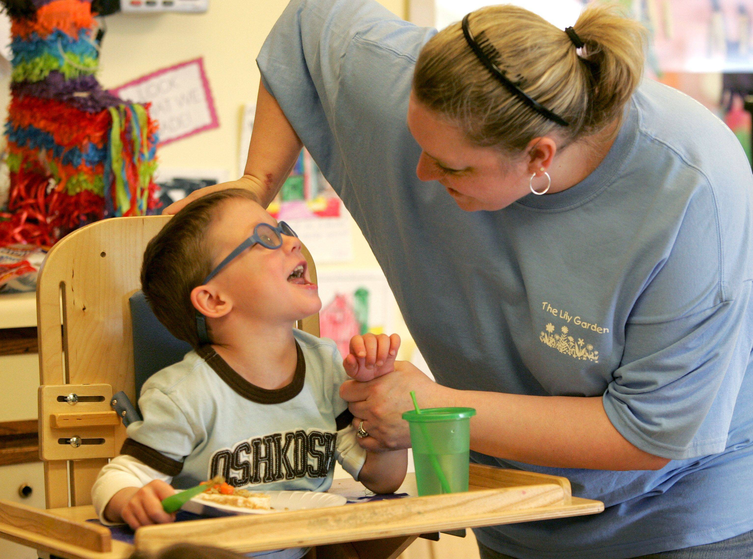 Kelly Lopresti, director of the Lily Garden child care center at Easter Seals in Villa Park, greets Charlie Krupka, 4.