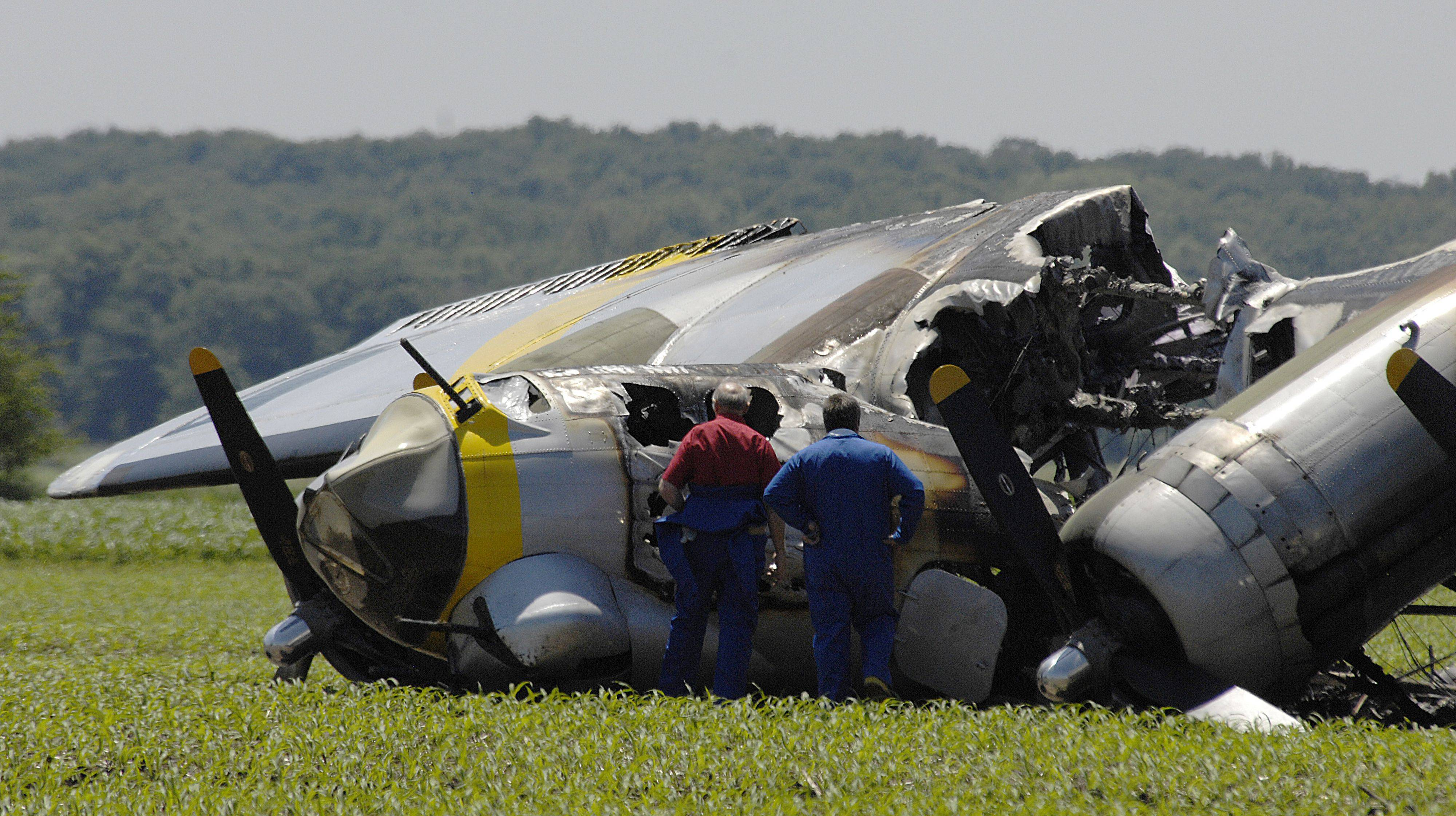 Investigators view the wreckage of the vintage B-17 airplane that made an emergency landing in a cornfield near Oswego.