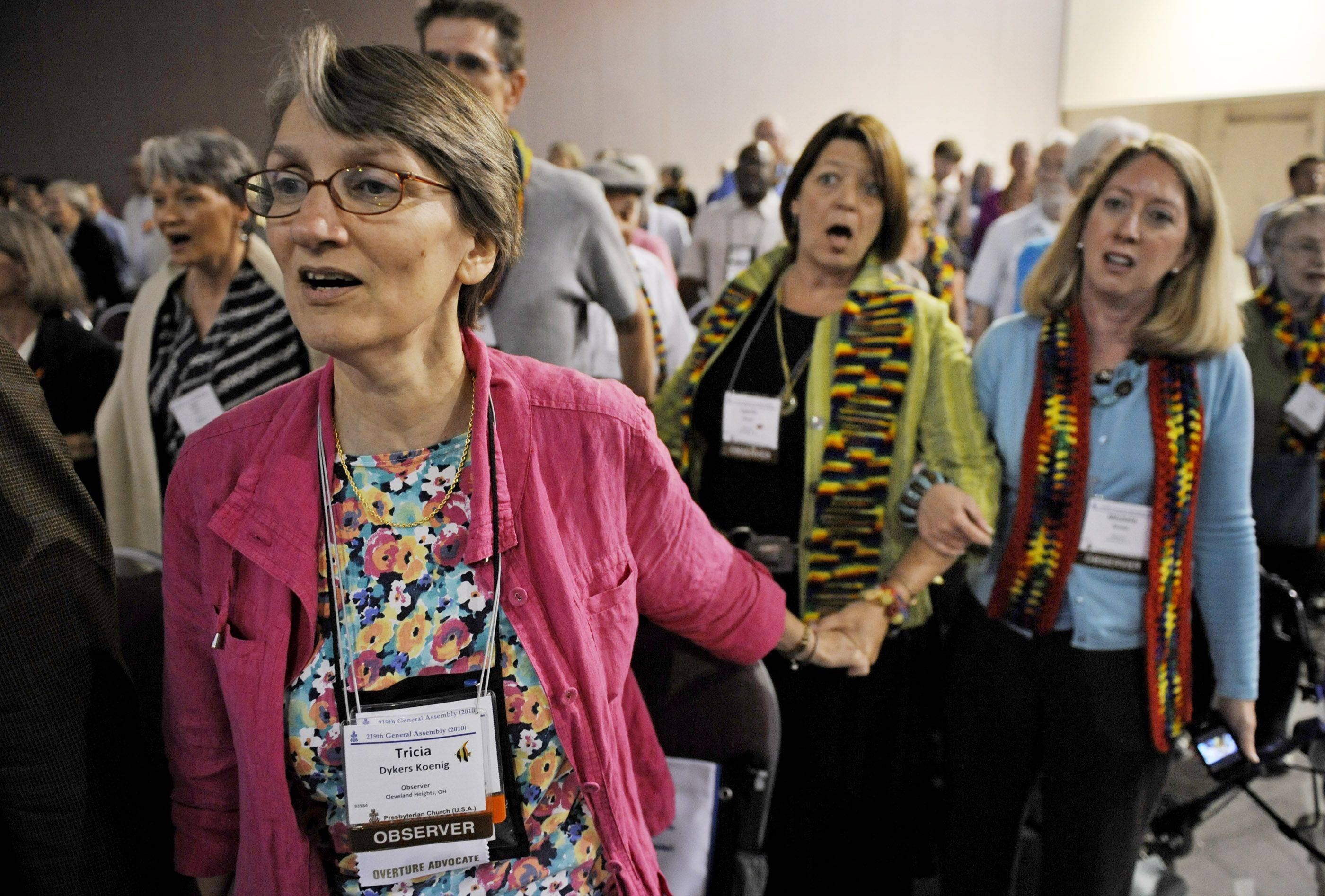 Observers Tricia Dykes Koenig, left, and Michelle Ready, right, and Laurie Kraus join in a hymn after the General Assembly of the Presbyterian Church last year in Minneapolis voted to approve lifting the church's ban on ordaining noncelibate gays and lesbians as clergy.
