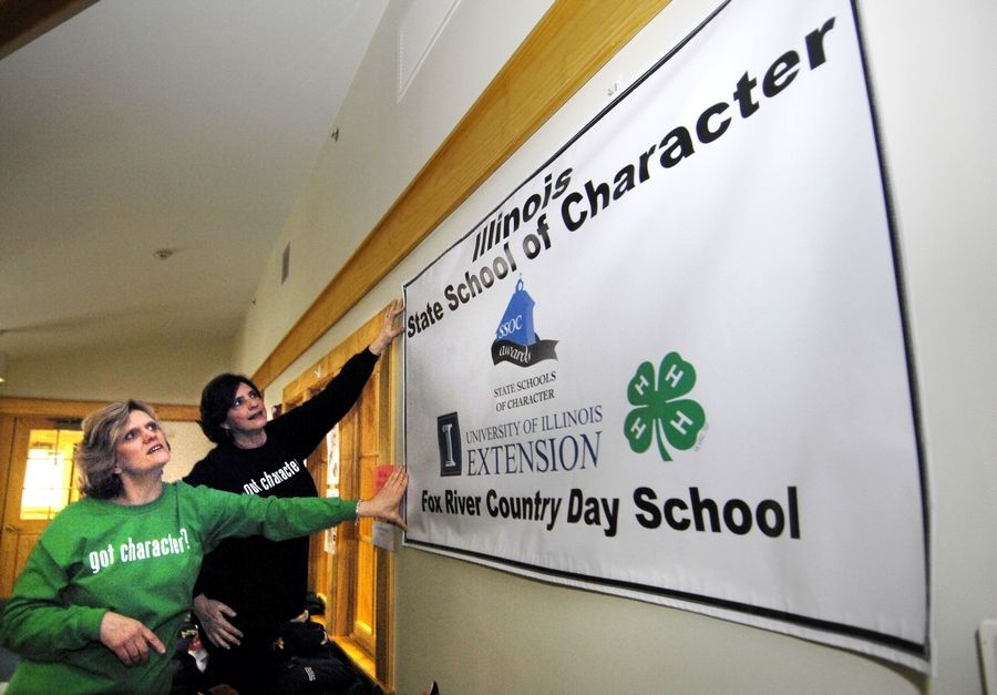 Karen Morse, head of Fox River Country Day School, left, and Jaime Switzer, director of development, hang a new banner in the lobby of the school after winning the 2011 State School of Character award from the University of Illinois Extension. Only one other school in the state got the award.