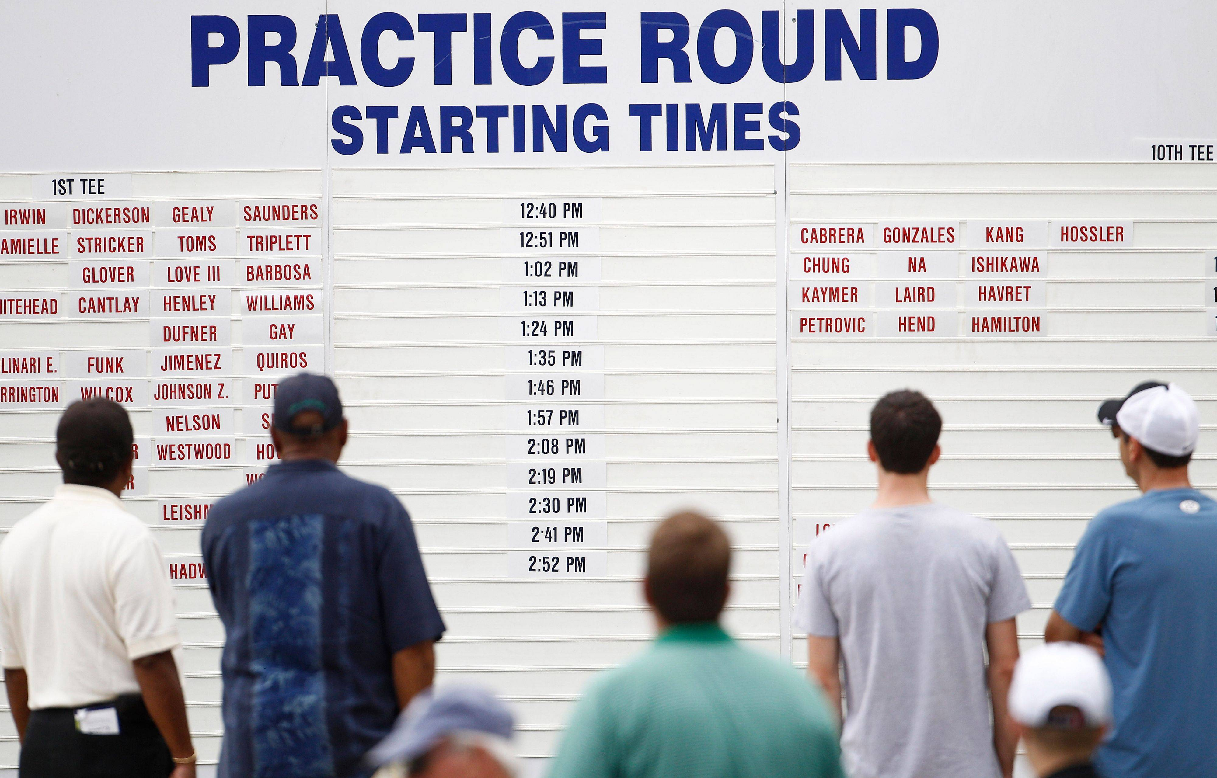 Fans look at the starting board during a practice round for the U.S. Open Championship golf tournament in Bethesda, Md.