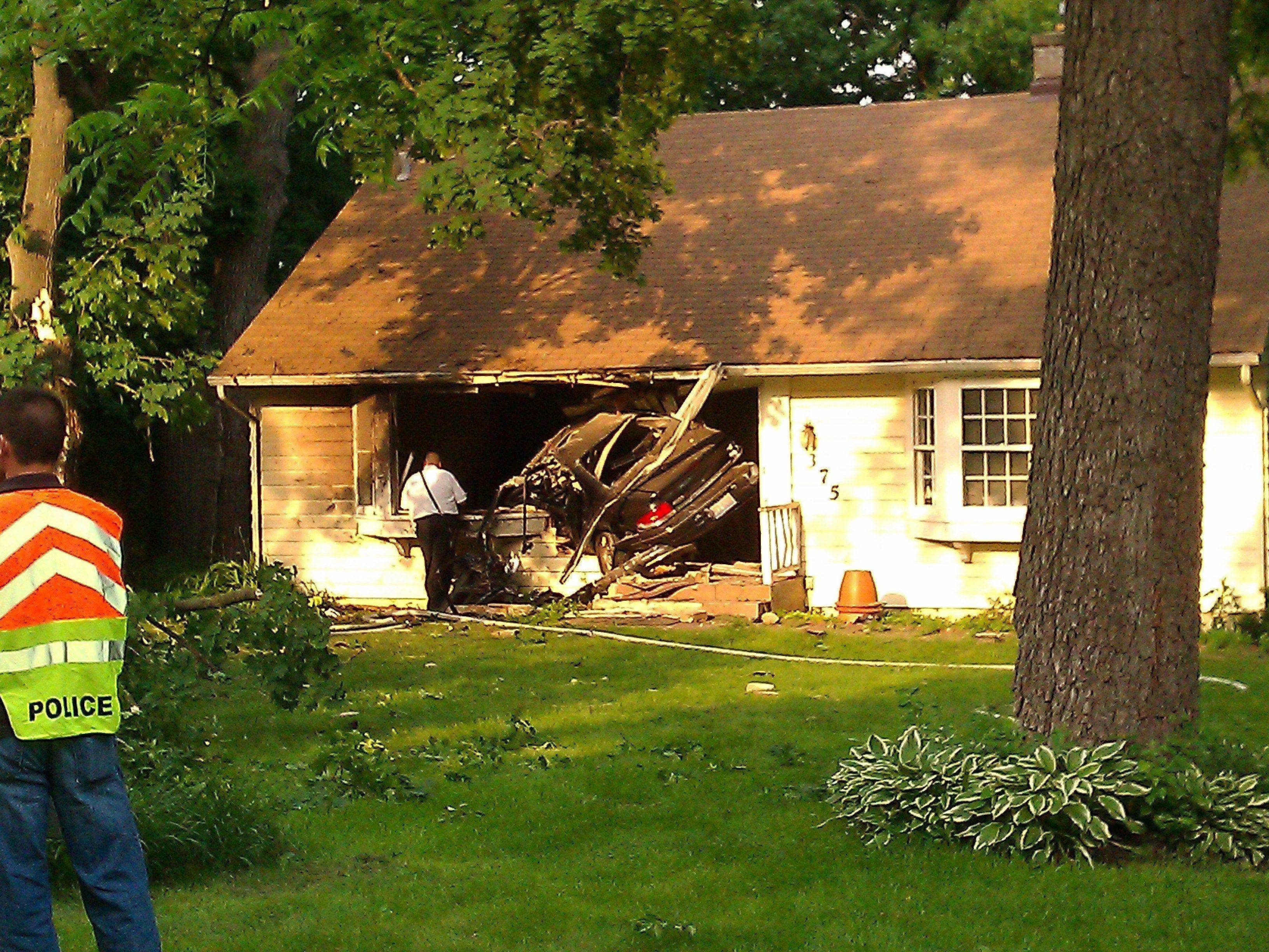 Personnel examine the scene where a vehicle struck a house along Route 31 at Mooseheart Road in North Aurora on Tuesday.