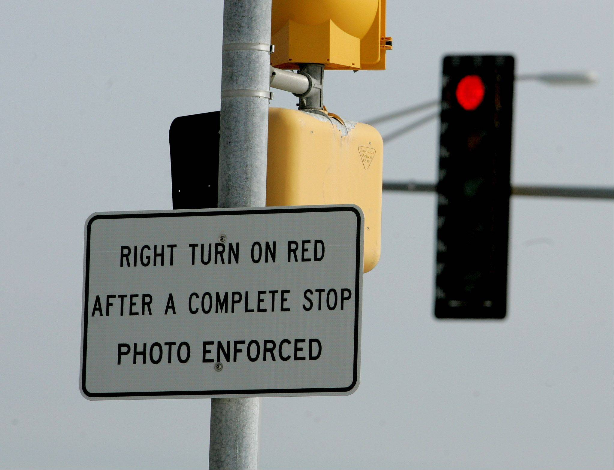 Signs at the intersection of Aurora Avenue and Fort Hill Drive in Naperville warn drivers about red-light cameras that have been installed.