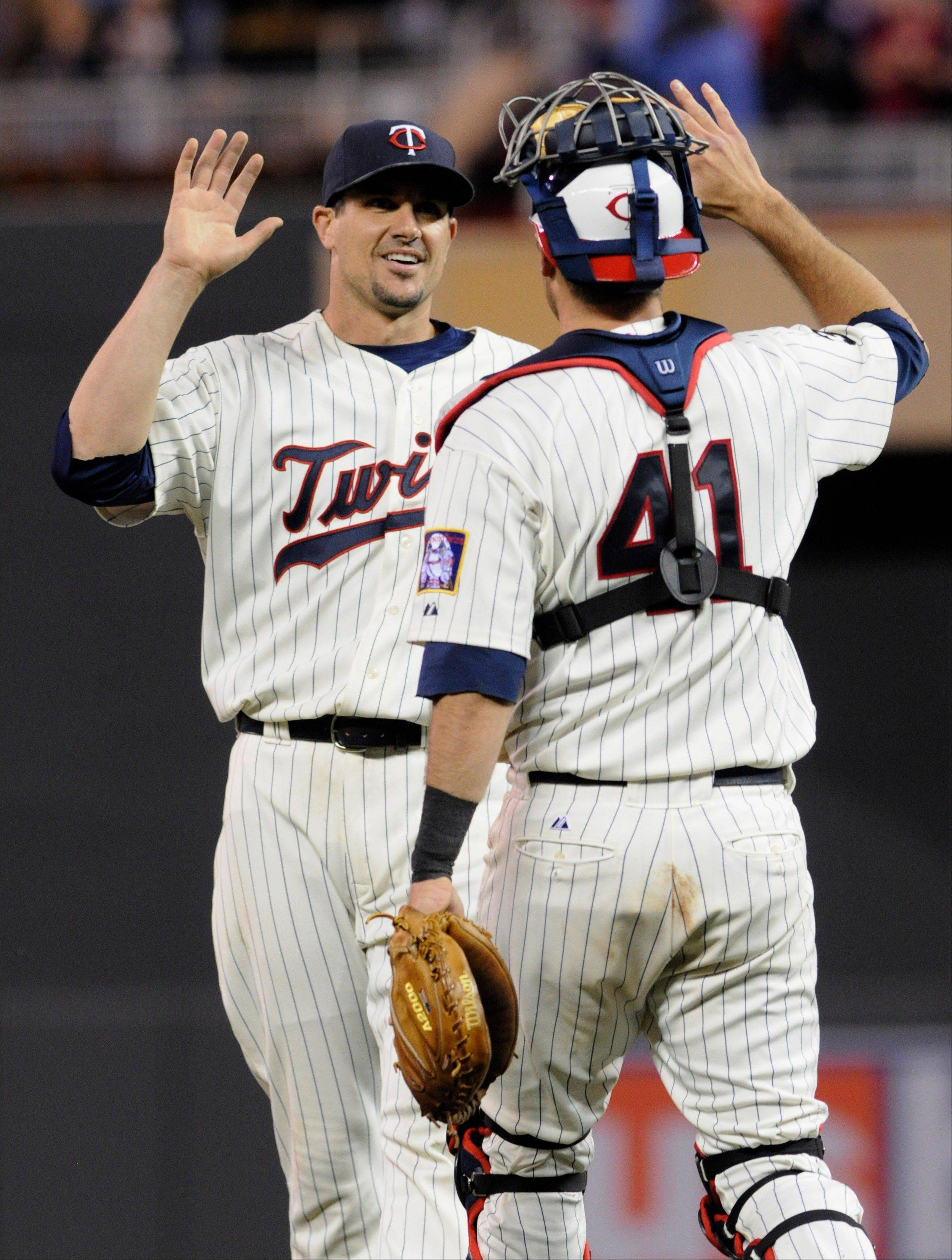 Minnesota Twins pitcher Carl Pavno, left, and catcher Drew Butera celebrate their 4-1 win over the White Sox Wednesday. The Twins have had the Sox number of late.