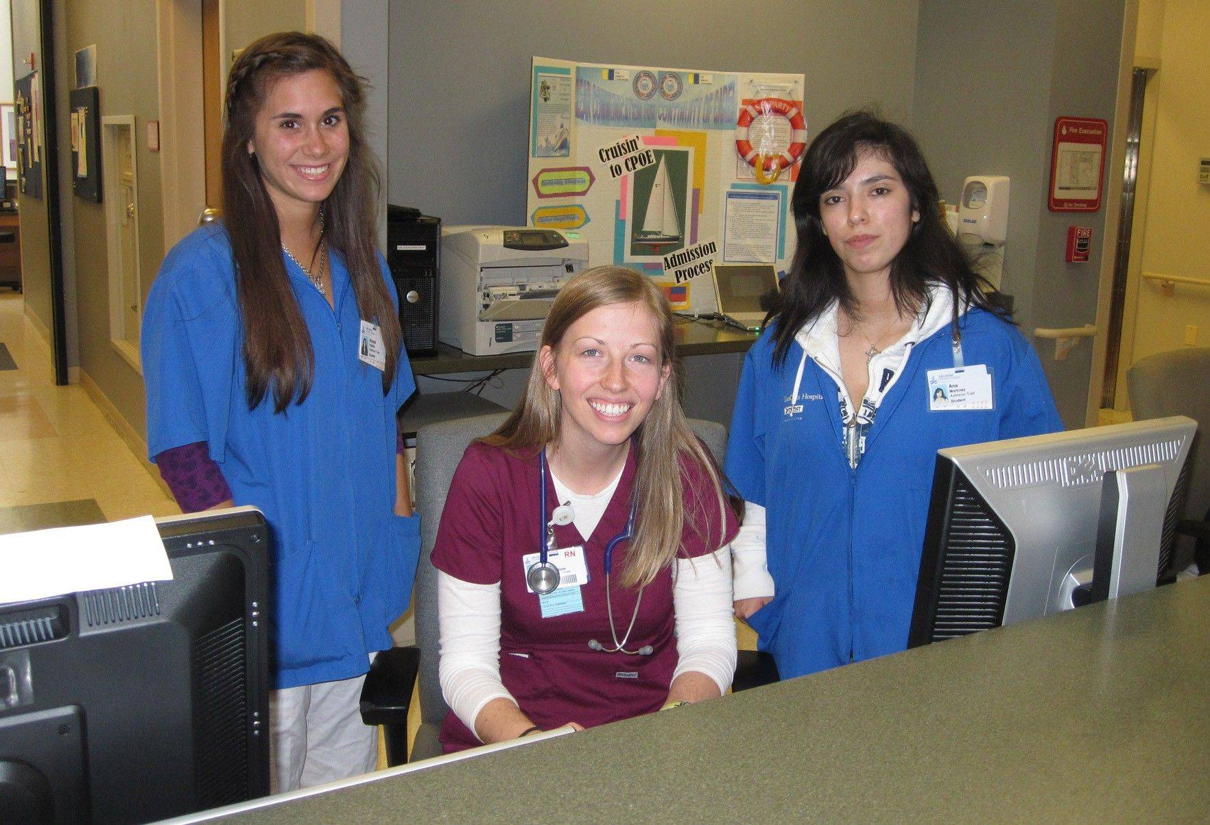 Addison Trail High School students Alyssa Padilla, left, and Ana Martinez, right, learn about career options from Diane Ream, an emergency room nurse at Adventist GlenOaks Hospital. The school and hospital formed a partnership 20 years ago to give students real-world exposure to healthcare careers.