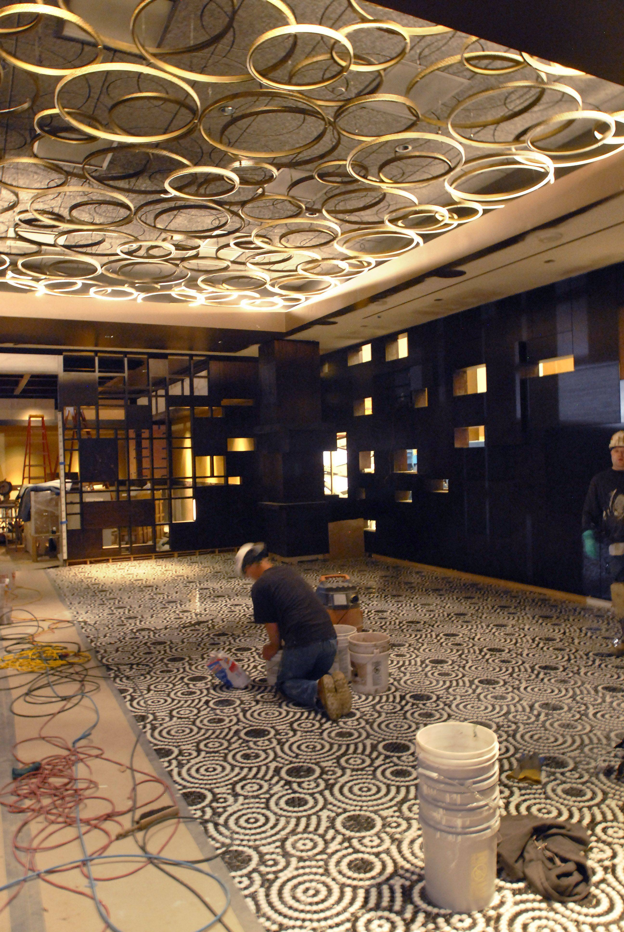 A worker installs a mosaic tile floor in the upscale Hugo's Frog Bar and Chophouse, which is part of the Gibson's Restaurant Group, that will feature steaks and seafood. At left, FLIPT will be a casual grill serving freshly made burgers, sandwiches, fries and shakes.