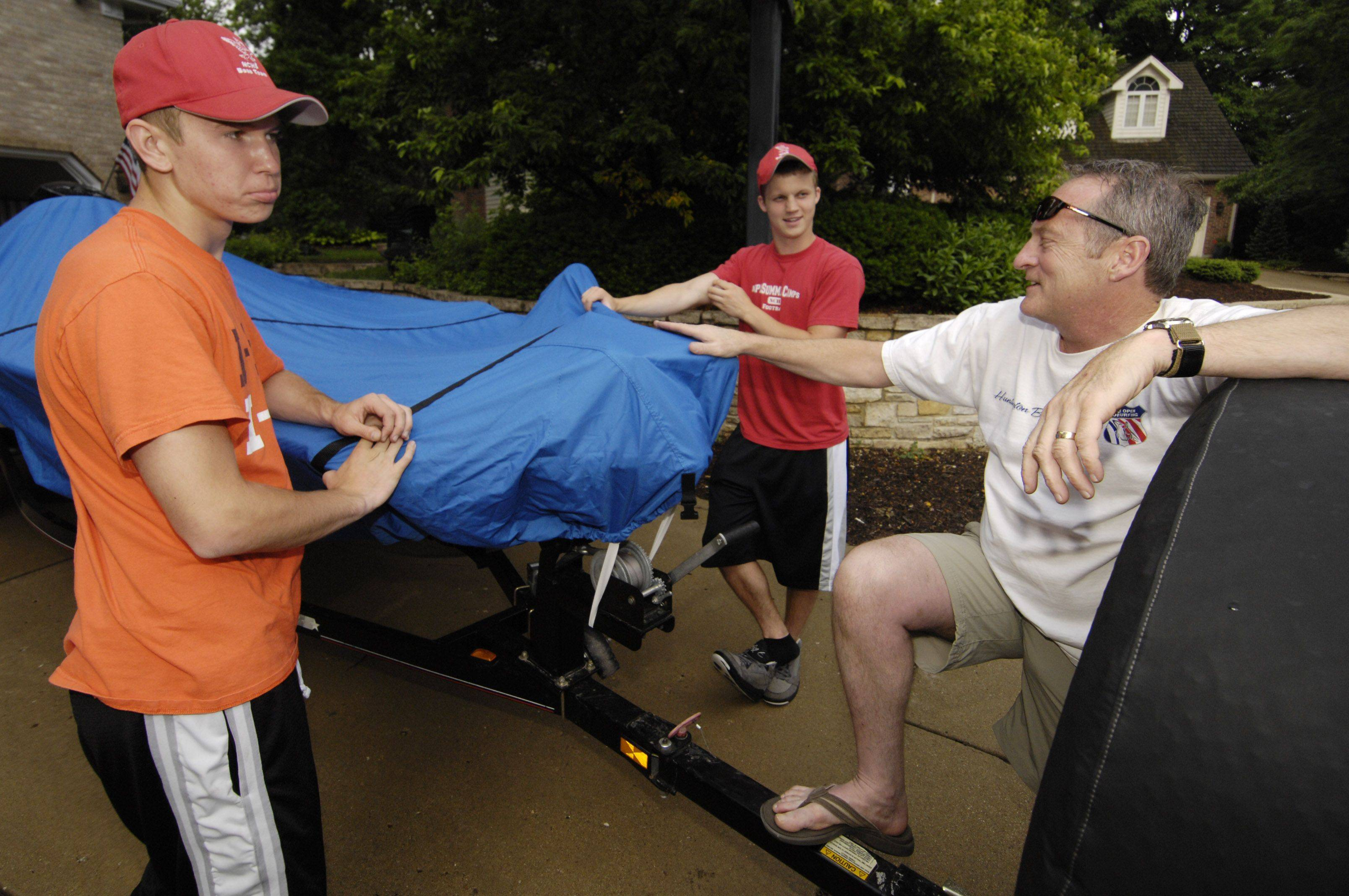 Naperville Central bass fishing team members Charlie Sterrett and Andrew Mlotek, along with coach Brian Bakke, ready a boat Wednesday evening for the trip to the state finals at Carlyle Lake.