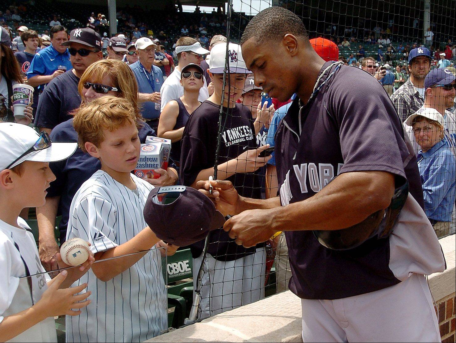 Bob Chwedyk/bchwedyk@dailyherald.comCurtis Granderson of the Yankees signs autographs for some youngsters before the Cubs vs. Yankees game at Wrigley Field.