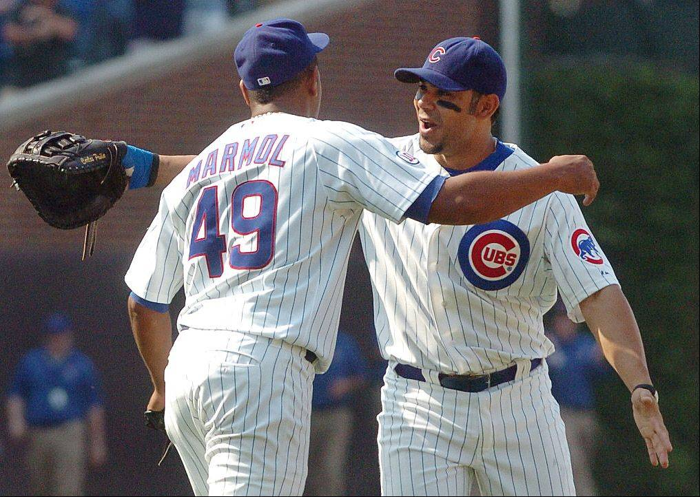 Carlos Pena congratulates Carlos Marmol on striking out the final batter to preserve the victory over the Yankees at Wrigley Field.