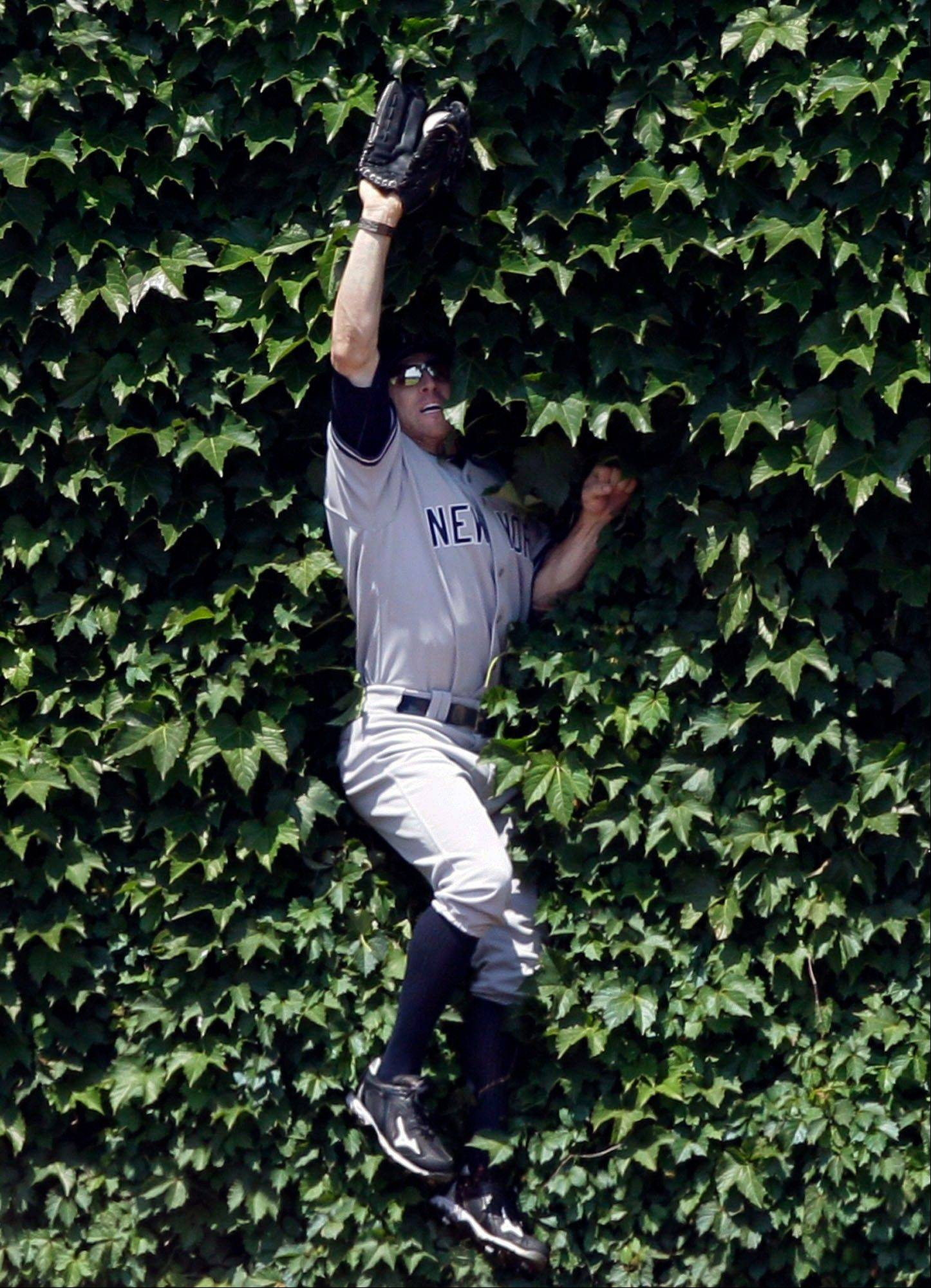 New York Yankees left fielder Brett Gardner makes a leaping catch in the ivy on the outfield wall on a hit by Chicago Cubs' Alfonso Soriano during the first inning of an interleague baseball game in Chicago, Friday, June 17, 2011.