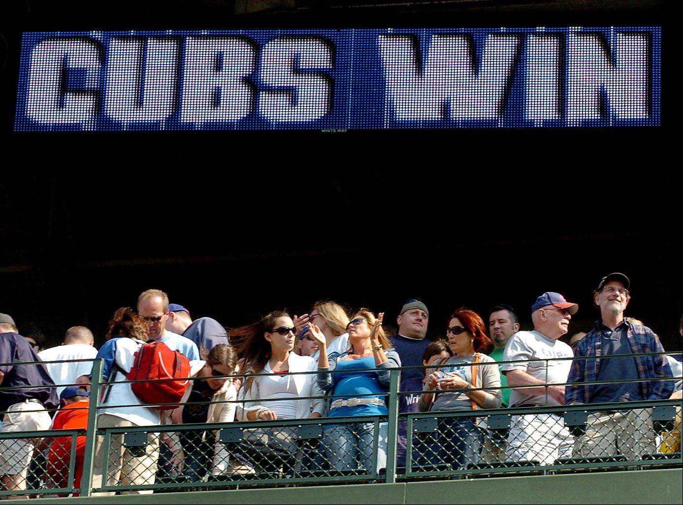 "Fans sing ""Go Cubs Go"" after Cubs defeat the Yankees 3-1 on Friday."