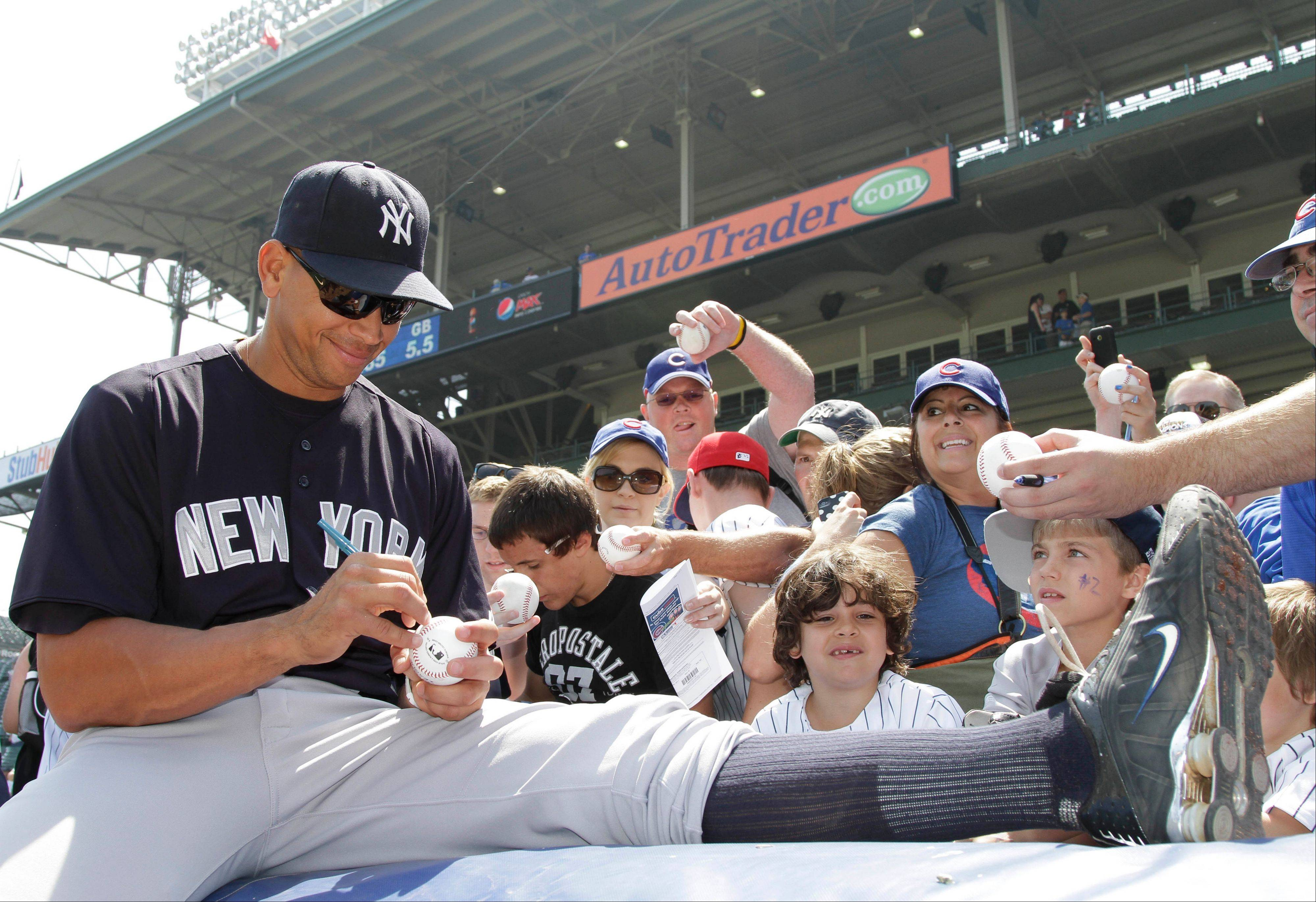 New York Yankees third baseman Alex Rodriguez signs autographs for fans before an interleague baseball game against the Chicago Cubs in Chicago, Friday, June 17, 2011.