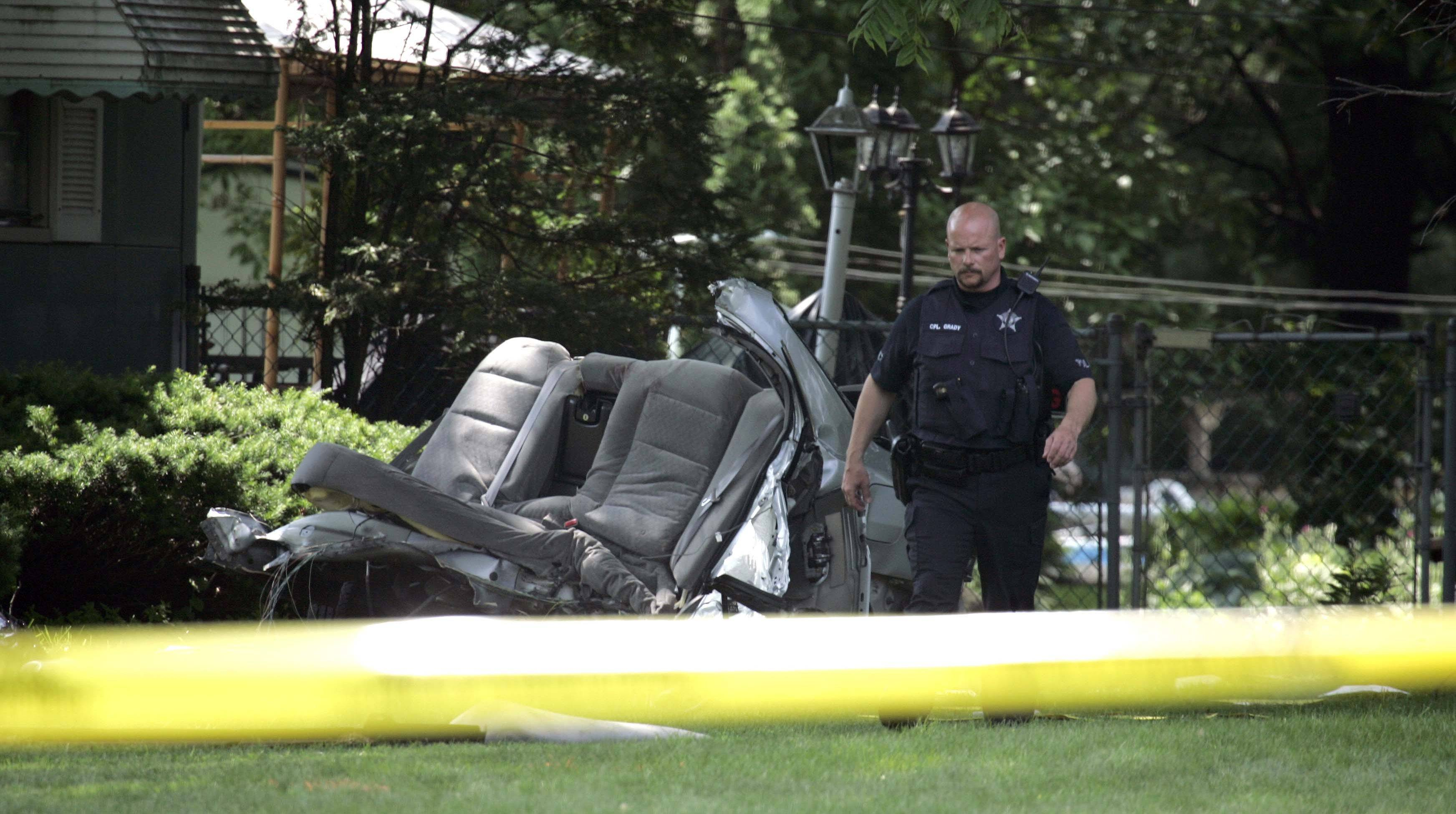 Prospect Heights police Cpl. Robert Grady inspects the scene of an accident where three teenagers died early Saturday. A fourth teen was hospitalized after the one-car accident on the 100 block of Camp McDonald Road in Prospect Heights.