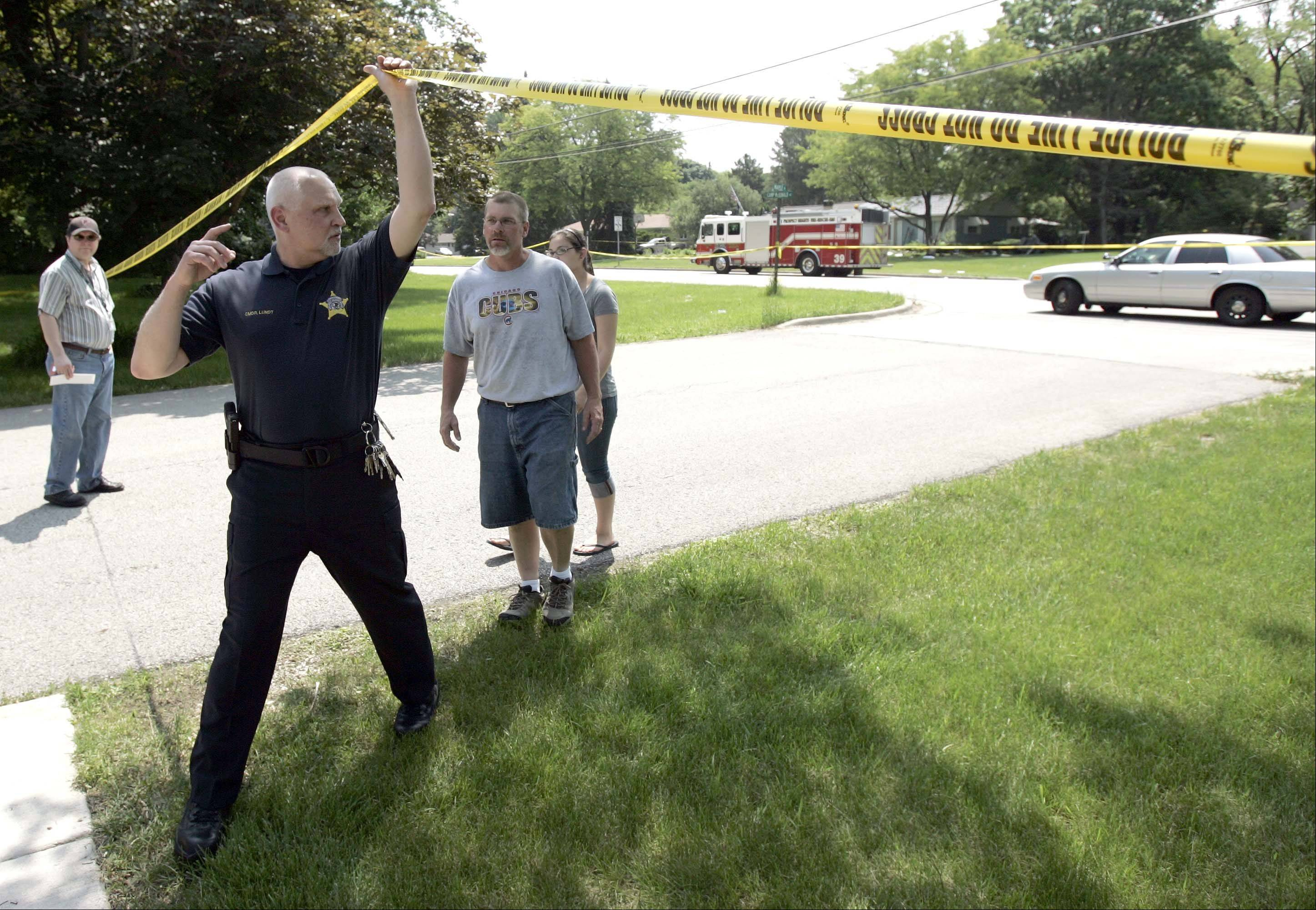 Prospect Heights Police Cmdr. Eric Lundt lifts the police tape for Scott Nielsen and his daughter Laura, 15, to talk to the media Saturday morning.