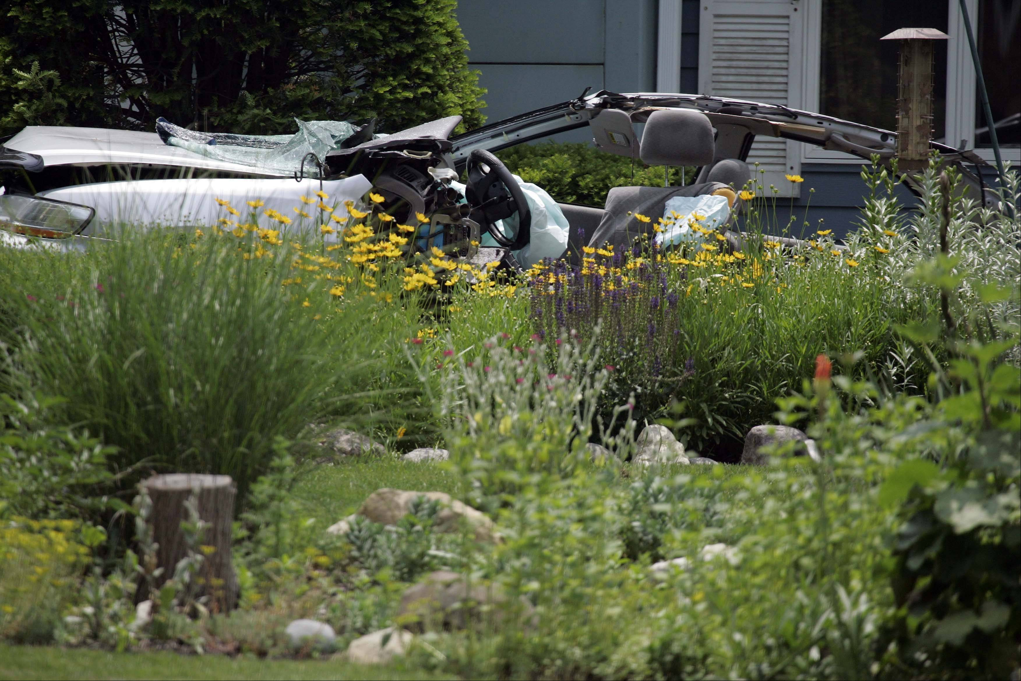Part of the car sits in the flower bed of the home where three teens died early Saturday in Prospect Heights