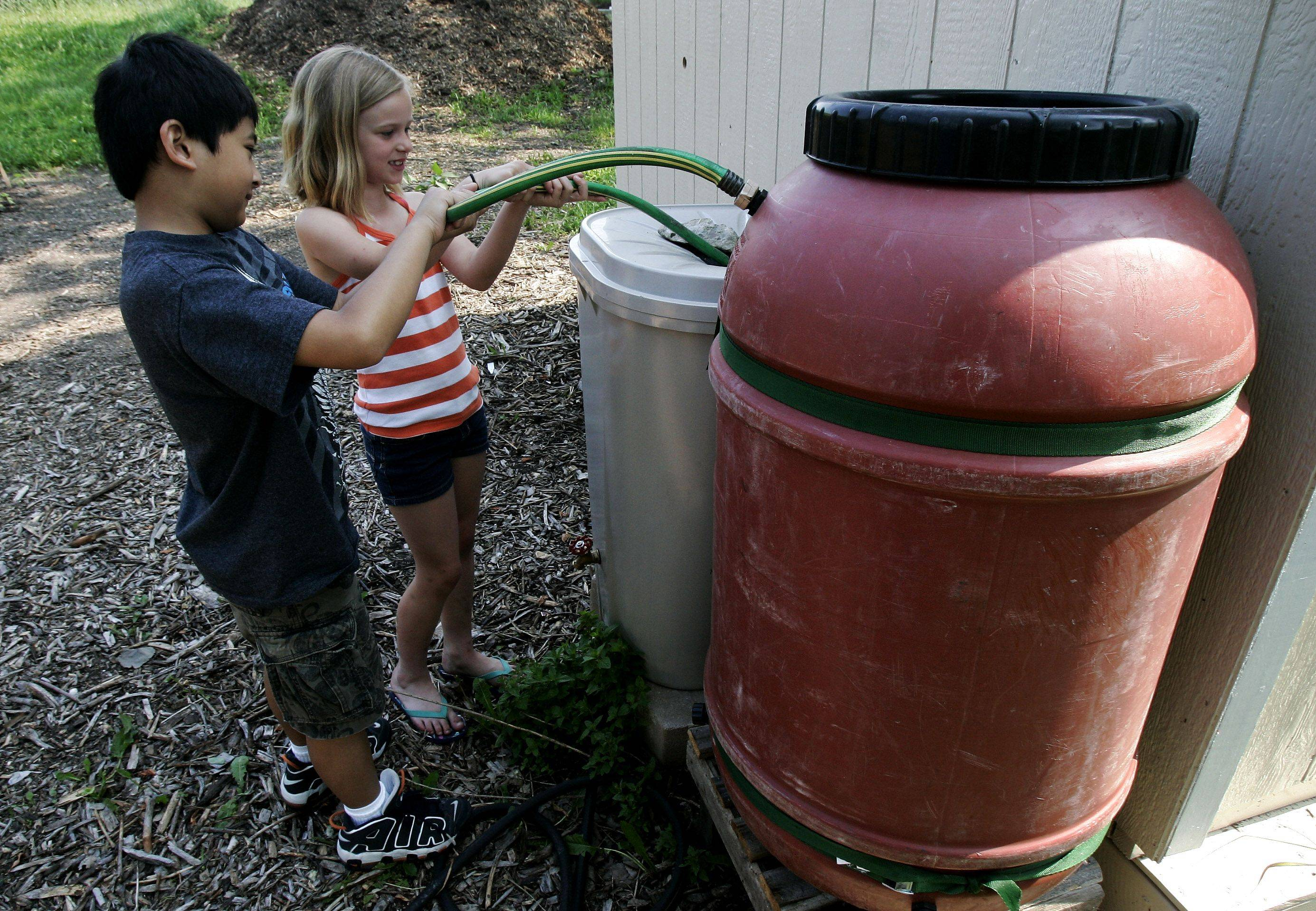 Malcolm Mazan, left, and Caroline Sharpe, both 8, fill the overflow barrel from the main rain barrel as students tend to the garden at Woodland Elementary School West in Gages Lake to benefit the Giving Garden.