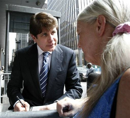 Former Illinois Gov. Rod Blagojevich signs an autograph as he departs the Federal Court building.