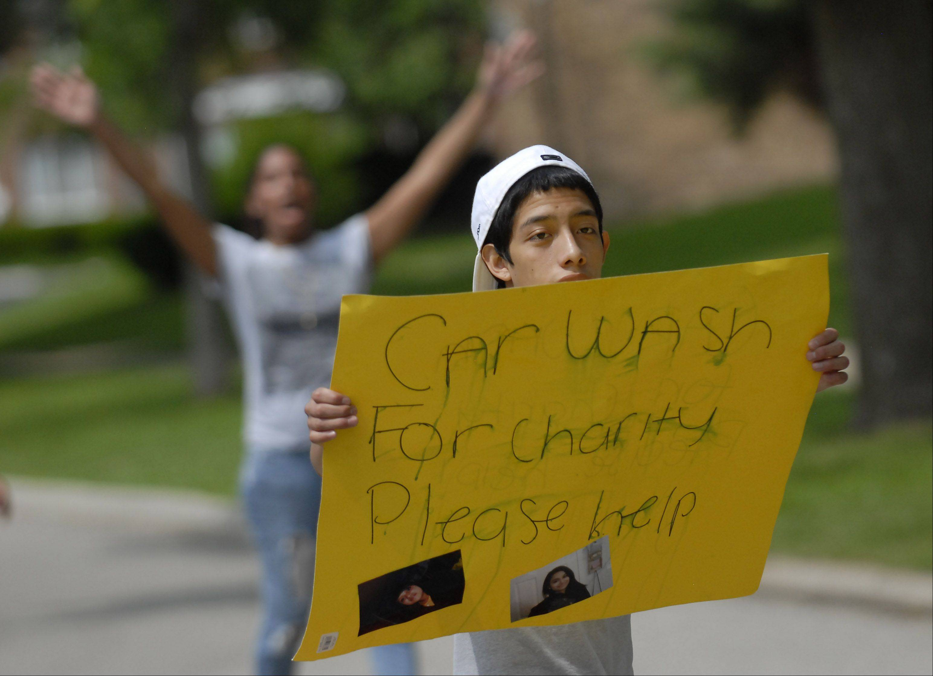 George Aparicio, 15, of Mount Prospect makes motorists aware of a carwash Monday to raise money for victims of a crash Saturday in Prospect Heights that took the lives of three teenagers.