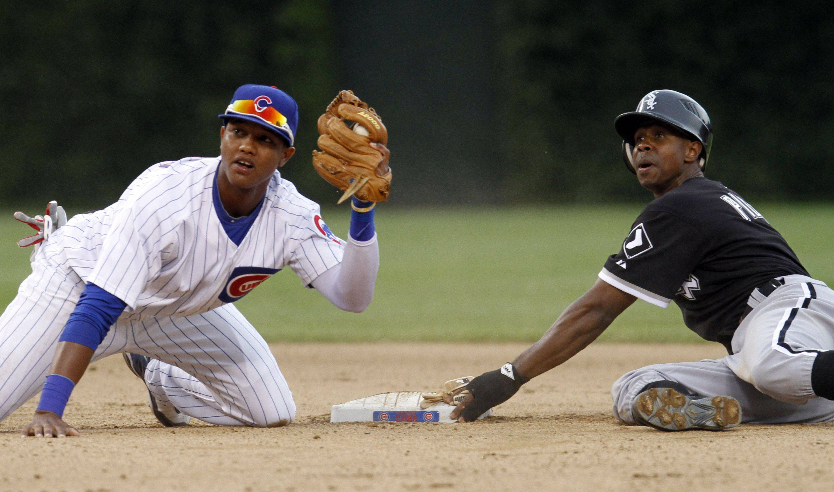 Chicago Cubs shortstop Starlin Castro, left, and Chicago White Sox's Juan Pierre look at second base umpire Kerwin Danley after Juan Pierre was safe stealing second during the seventh inning of an interleague baseball game in Chicago, Saturday, June 12, 2010. The White Sox won 2-0.