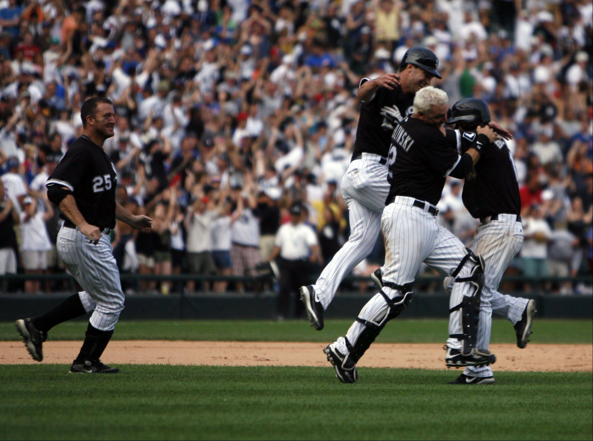 Chicago White Sox mob Gordon Beckham in the middle of field after he hit a game winning single in 8-7 win against the Cubs on Saturday June 27th.