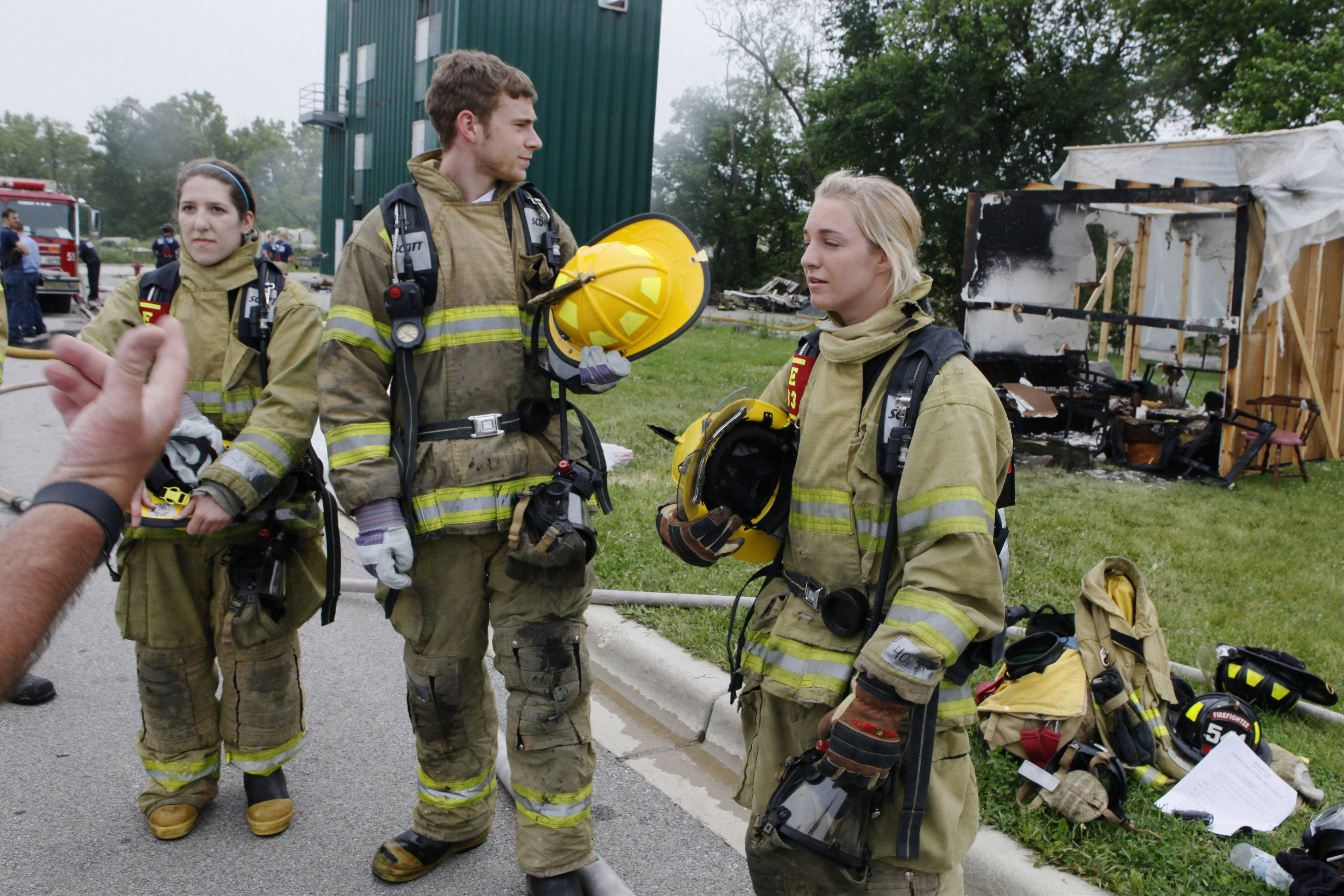 Megan Bannister, left, Brendan Bond and Erin Cinto listen to Aurora Local 99 personnel after extinguishing a simulated flashover.