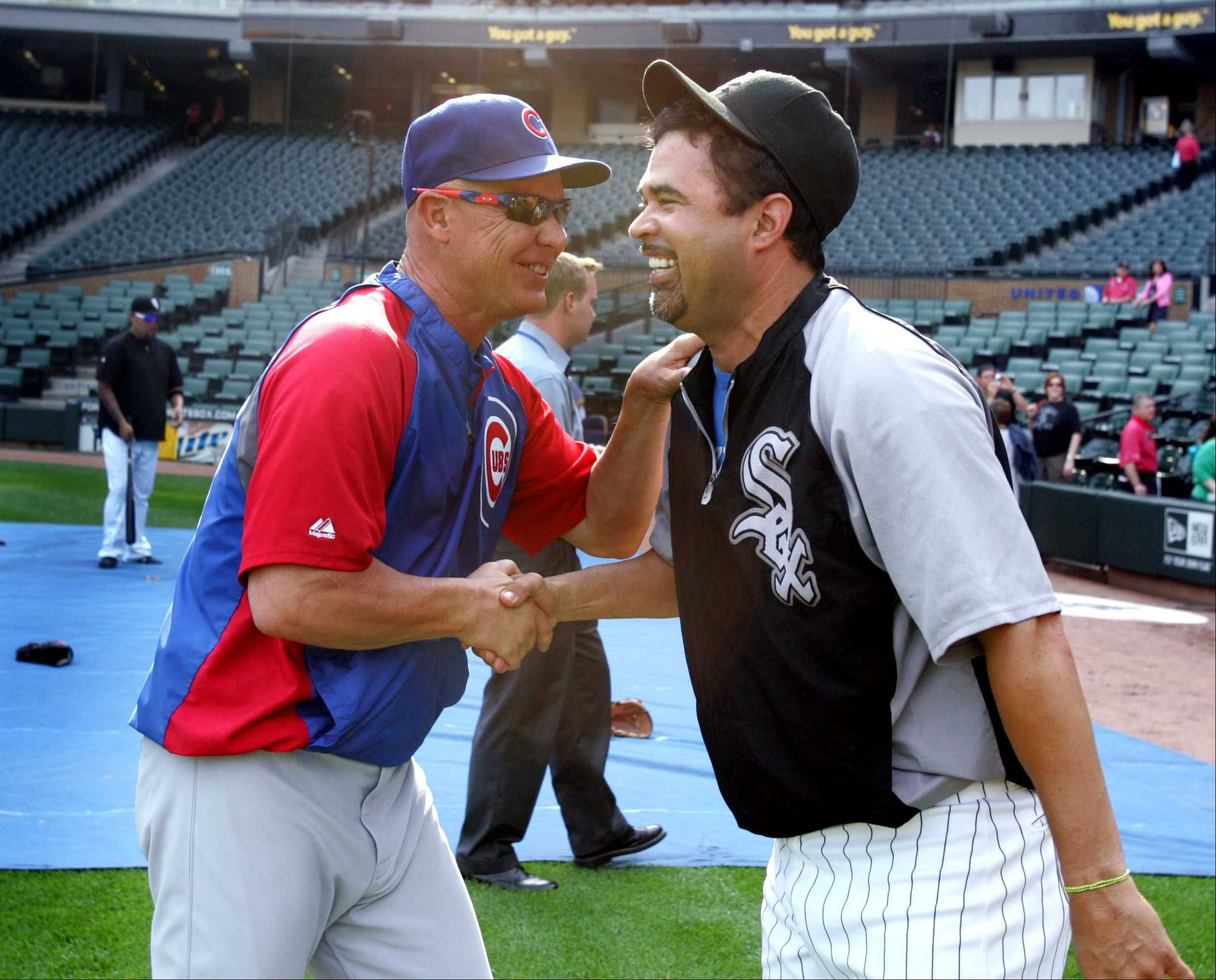 Chicago Cubs manager Mike Quade, left, greets Chicago White Sox manager Ozzie Guillen before the Crosstown Classic Monday at U.S. Cellular Field.