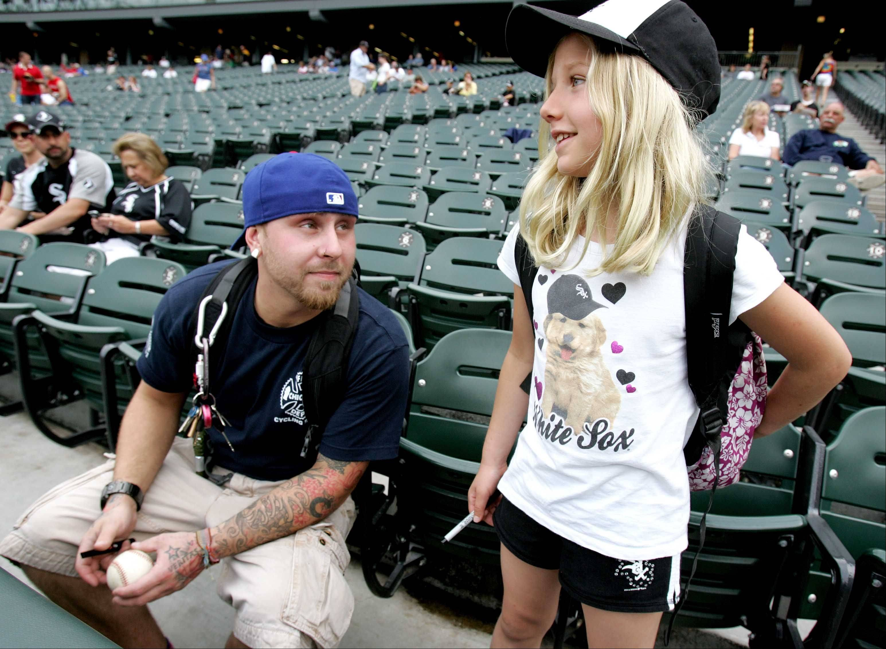 Cubs fan Jeff Ziesch, left of Chicago, chats with Sox fan Emmy Faber, 10 of Antioch, before Monday night's game at U.S. Cellular Field.