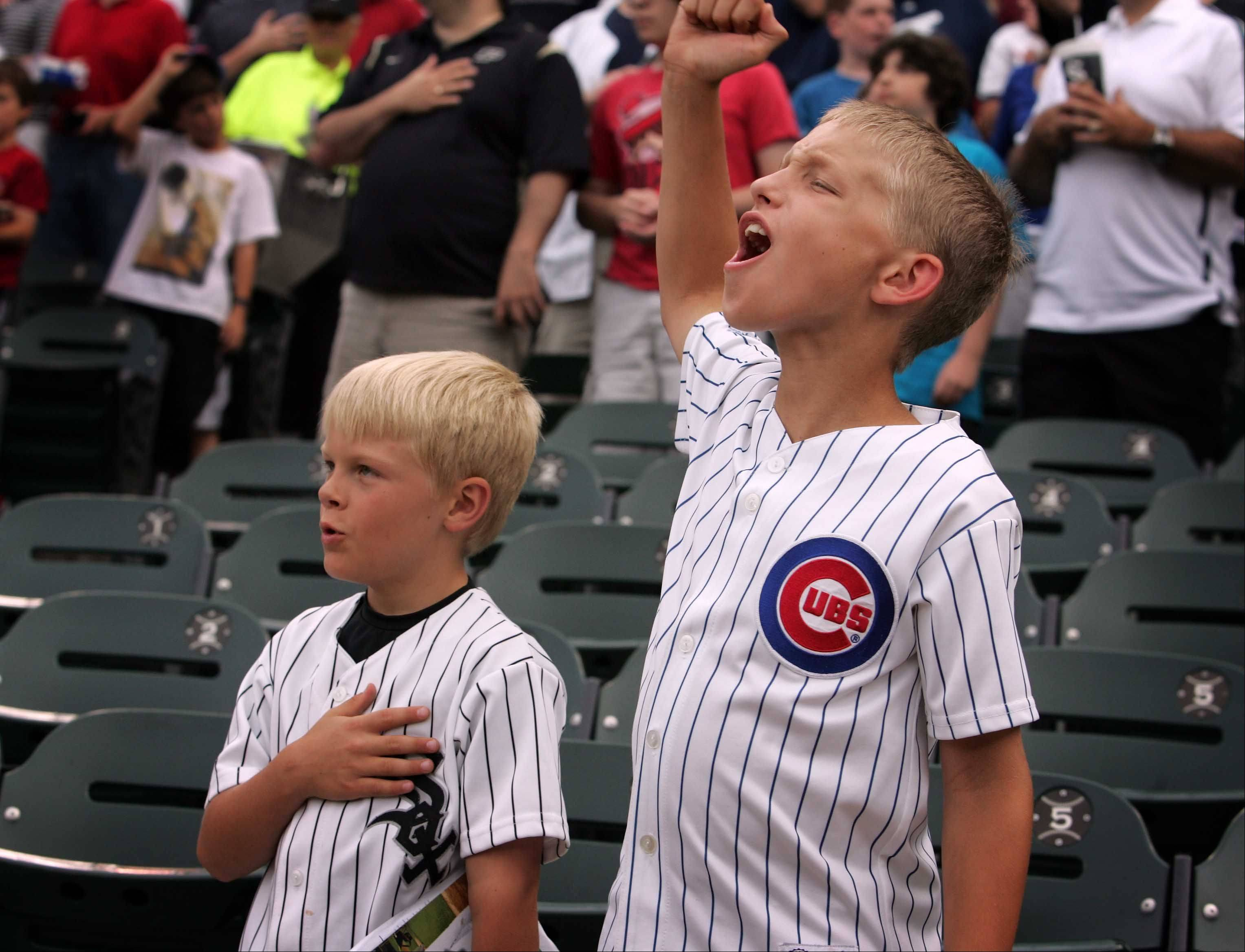 Naperville neighbors Jack Considine, 9, left, and Mark Gronowski, 9, cheer at the start of the Chicago Cubs and Chicago White Sox game Monday. This is the second game they have attended together.