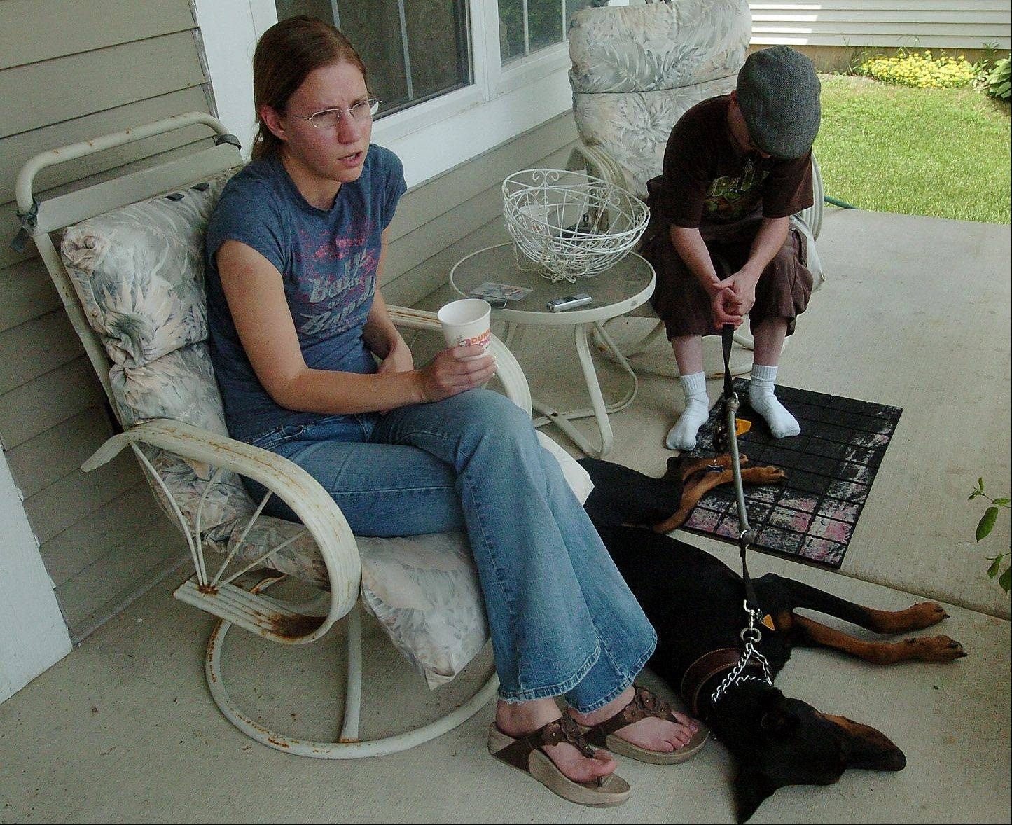 Taylor Stinchcomb's older sister, Mallorie Holler, talks Tuesday about Taylor on the front porch of their home in Gurnee, accompanied by a friend of the family, Casey Fallos, and Mallorie's Doberman, Renegade.