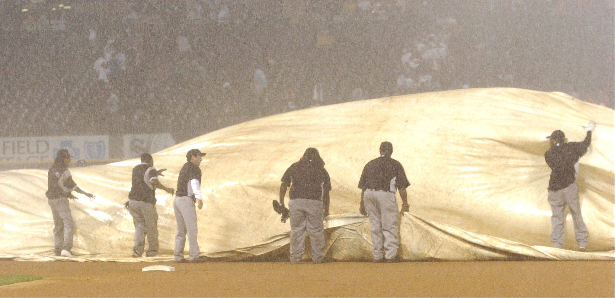 The grounds crew covers the field after a storm rolls in to delay the city series between the Chicago White Sox and Cubs at U.S. Cellular Field, in game 2.