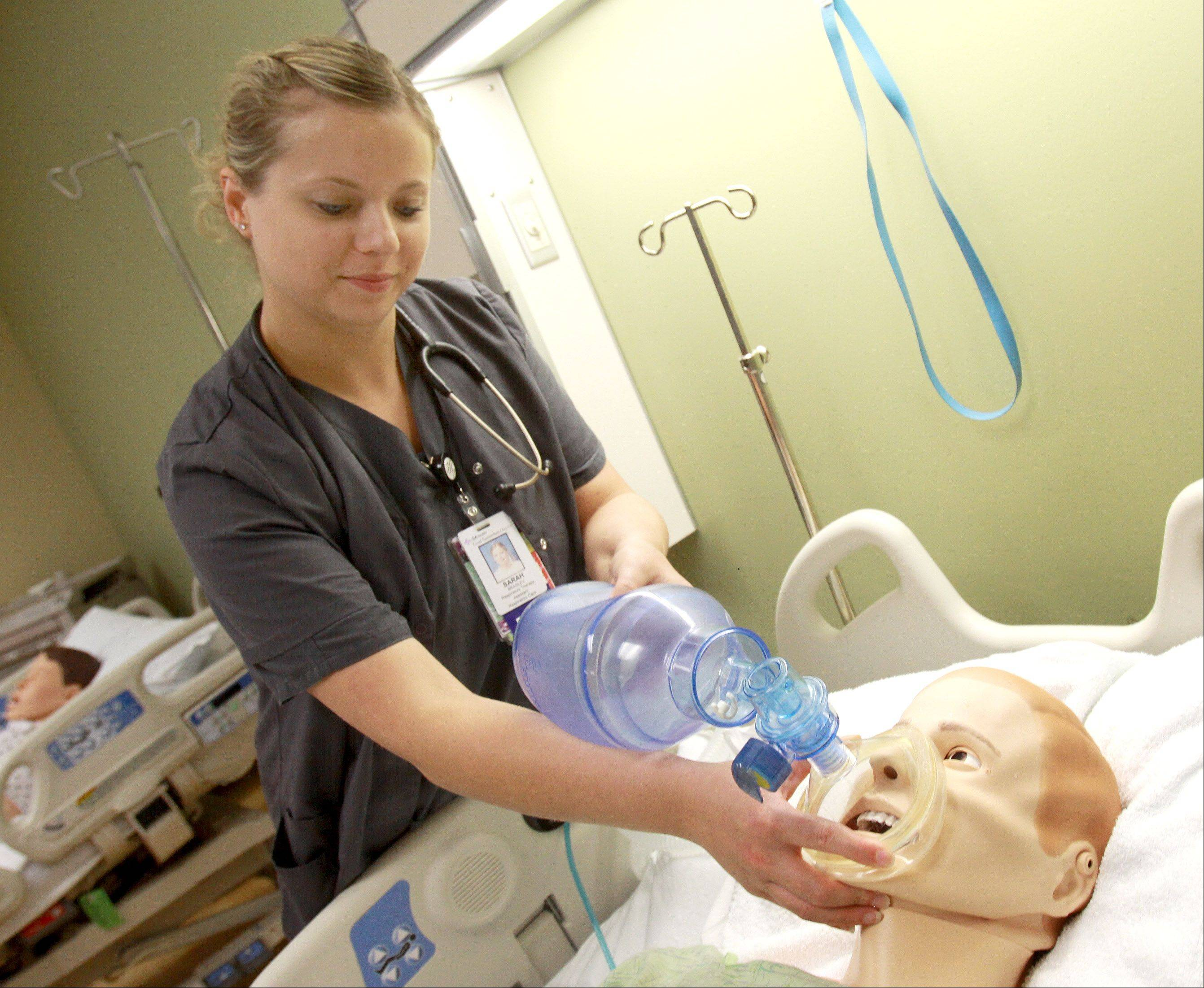 "Respiratory therapist Sarah Bradley gives oxygen to ""Malcolm,"" Advocate Good Samaritan's $100,000, high-tech simulator that responds like a real patient."